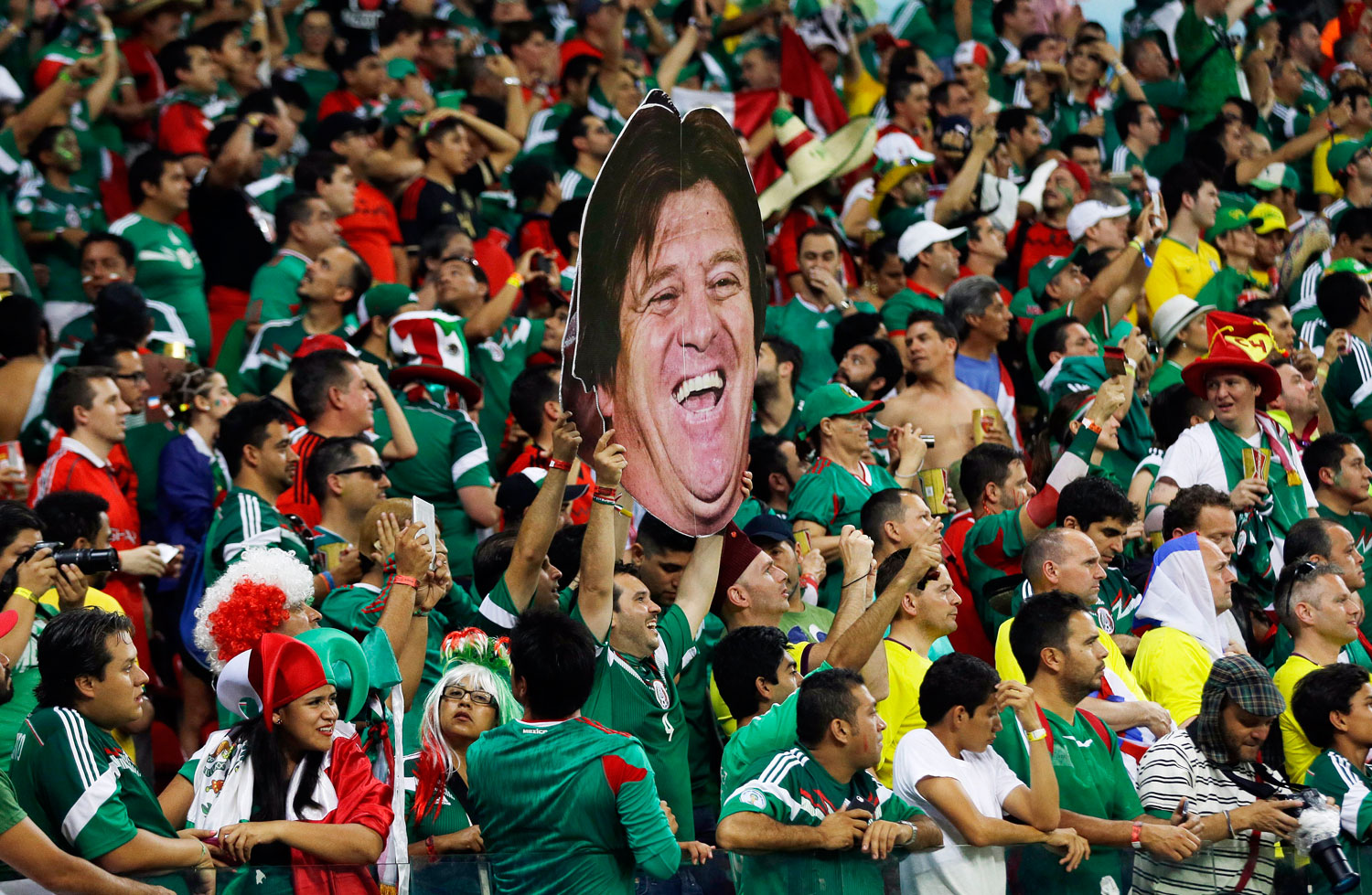 Mexico's fans celebrate holding a mask of Mexico's head coach Miguel Herrera after  the match between Croatia and Mexico at the Arena Pernambuco in Recife, Brazil on June 23, 2014.