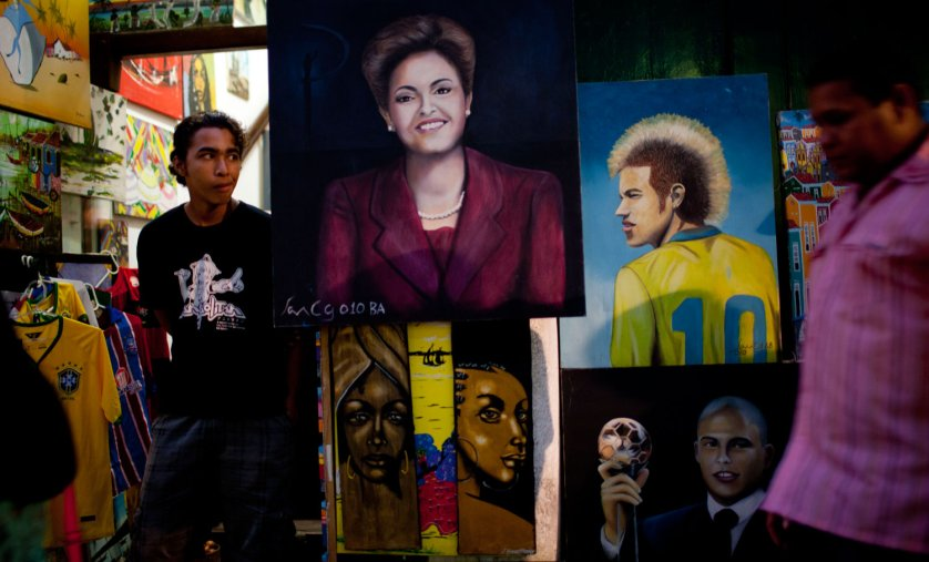 A man stands outside a shop selling paintings of Brazil's President Dilma Rousseff and Brazil's soccer player Neymar along a street decorated for the World Cup in the Pelourinho neighborhood of Salvador, Brazil on June 15, 2014.