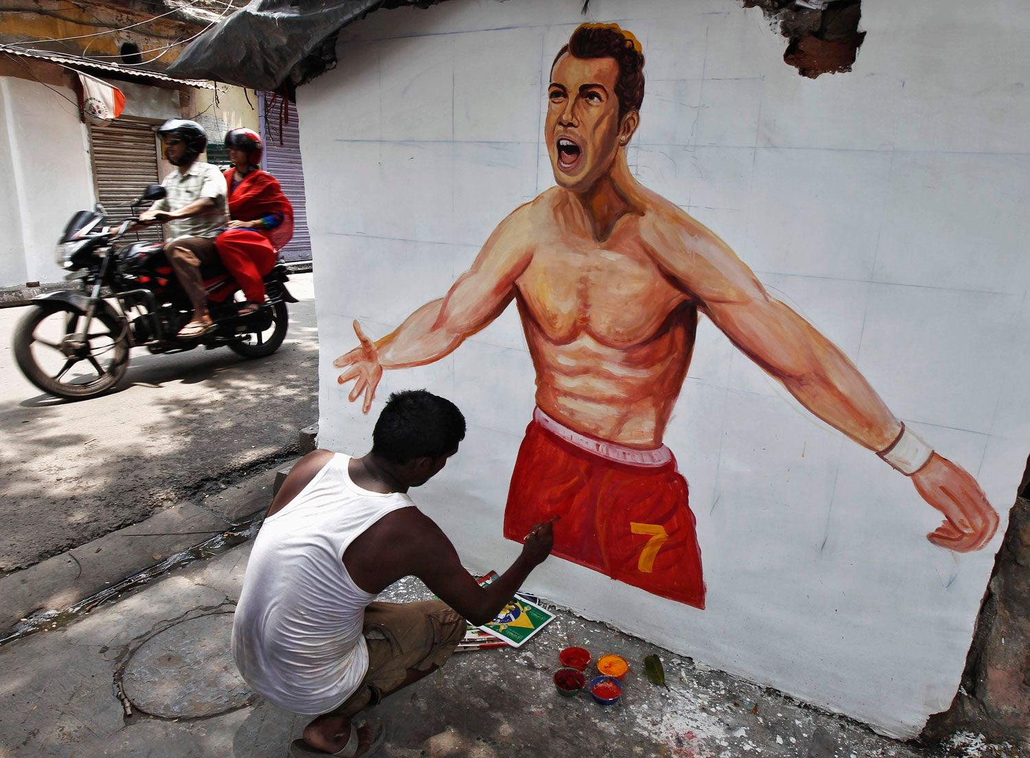 An artisan paints the wall of a house with a picture of Portugal's national soccer player Cristiano Ronaldo, in Kolkata on June 12, 2014.