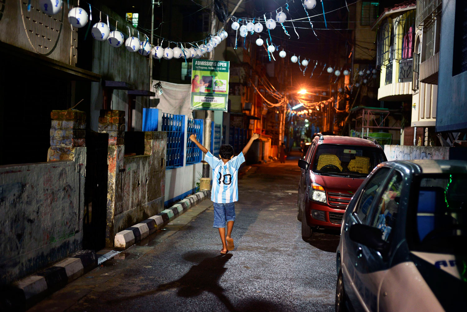 A young Indian football fan of Argentina in a Lionel Messi shirt walks back home after watching the Argentina-Iran match on a giant screen in Kolkata.