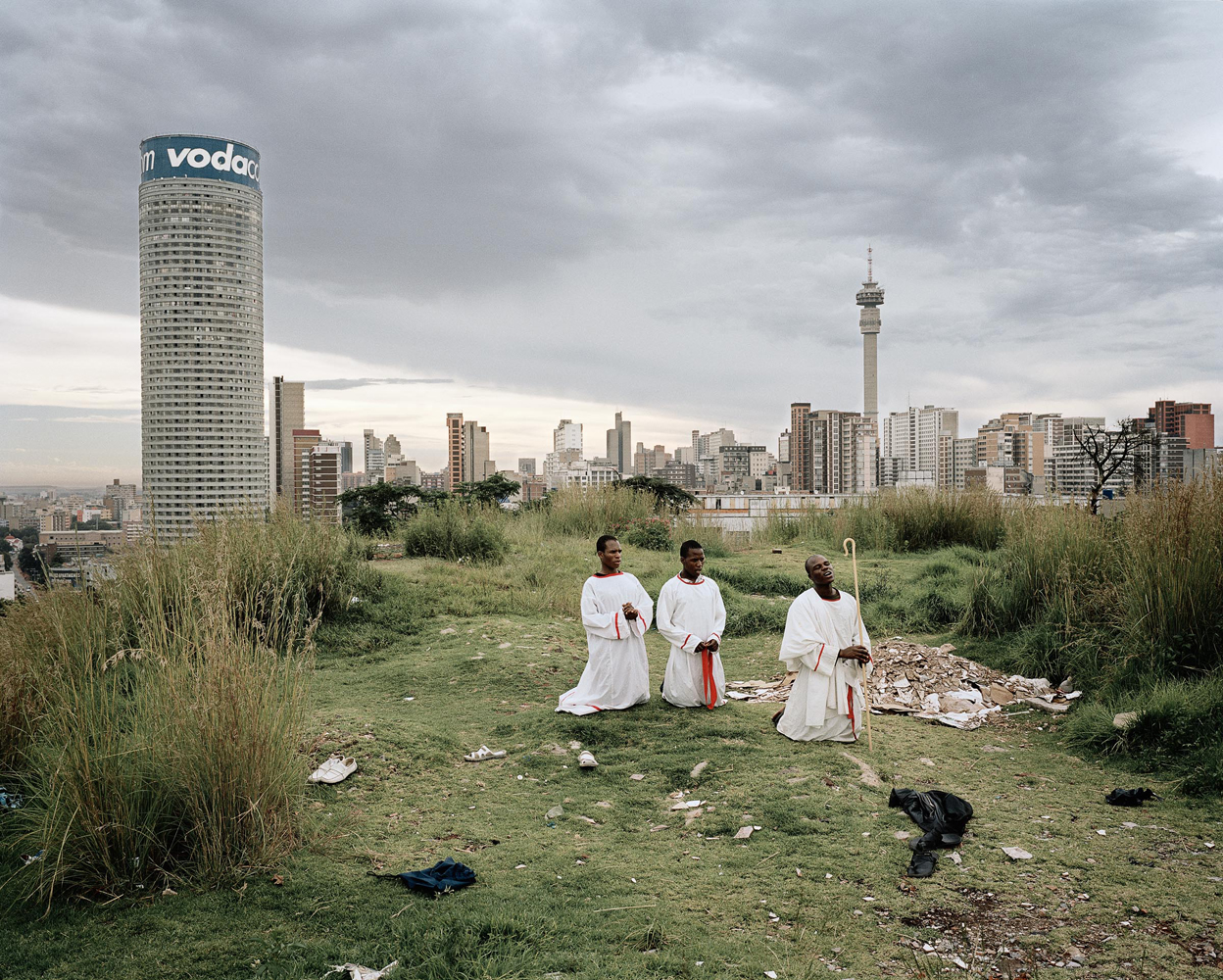 Ponte City, foregrounded by African Church members, and set against the Johannesburg skyline.