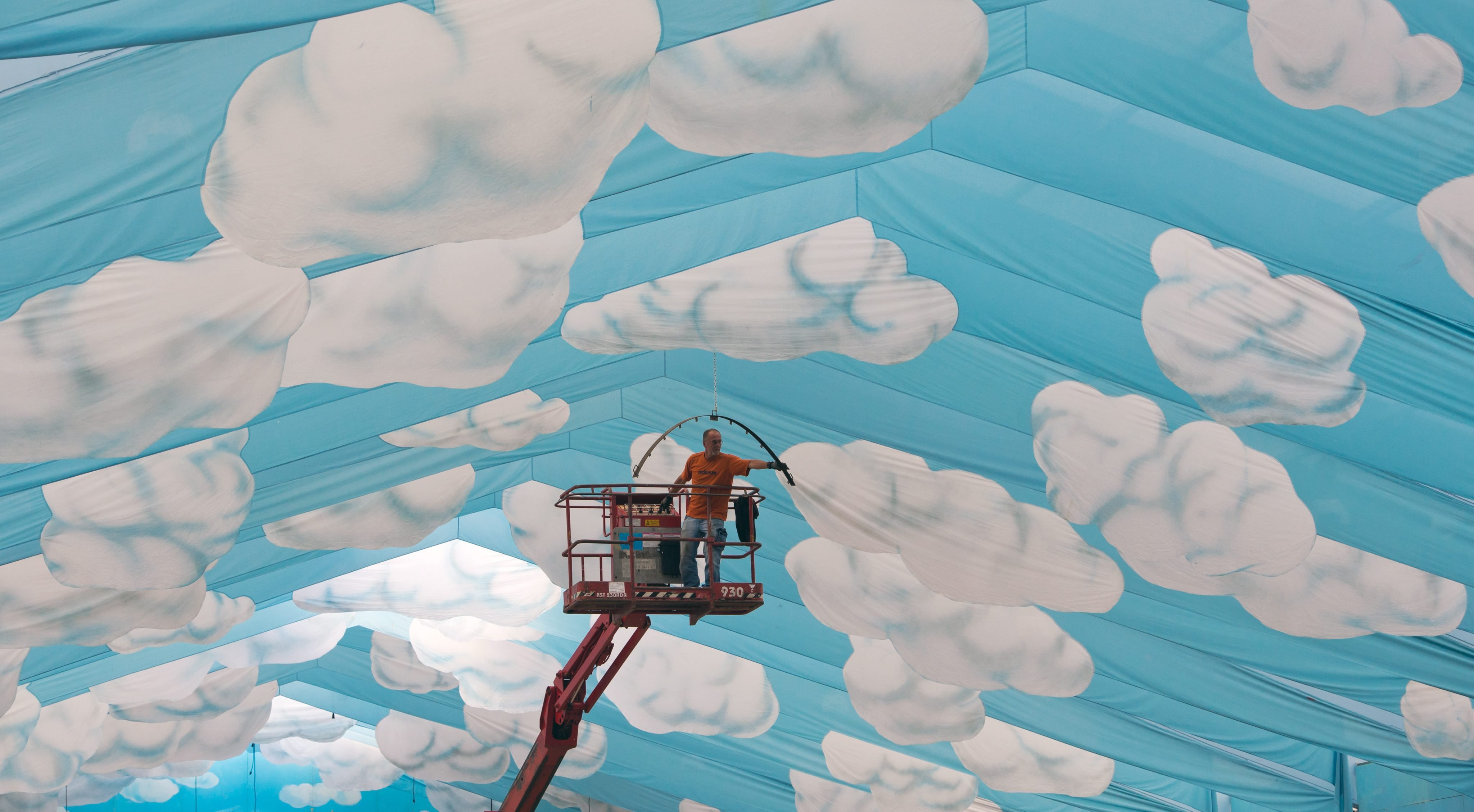 Aug. 4, 2014. A worker on a lift inspects the ceiling decoration with clouds pattern in a beer tent on the Oktoberfest grounds at Theresienwiese in Munich, Germany.