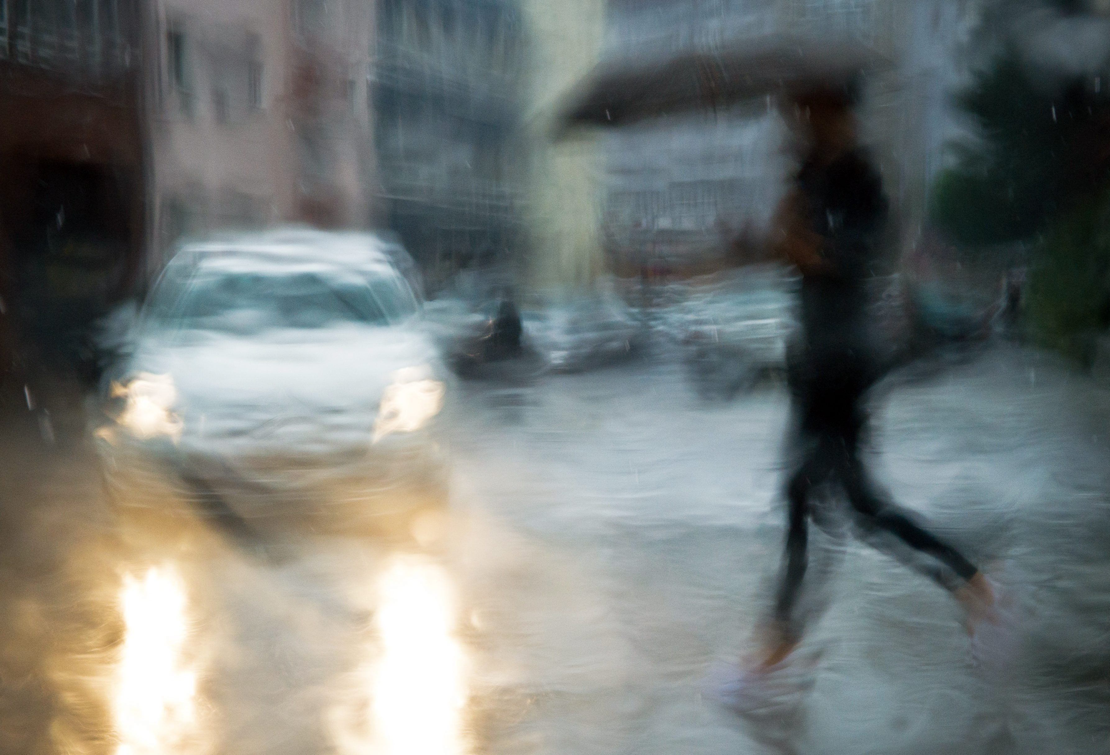 Aug. 4, 2014. A woman with an umbrella crosses a street in Hanover, Germany, photographed through the rain-wet window of a car.