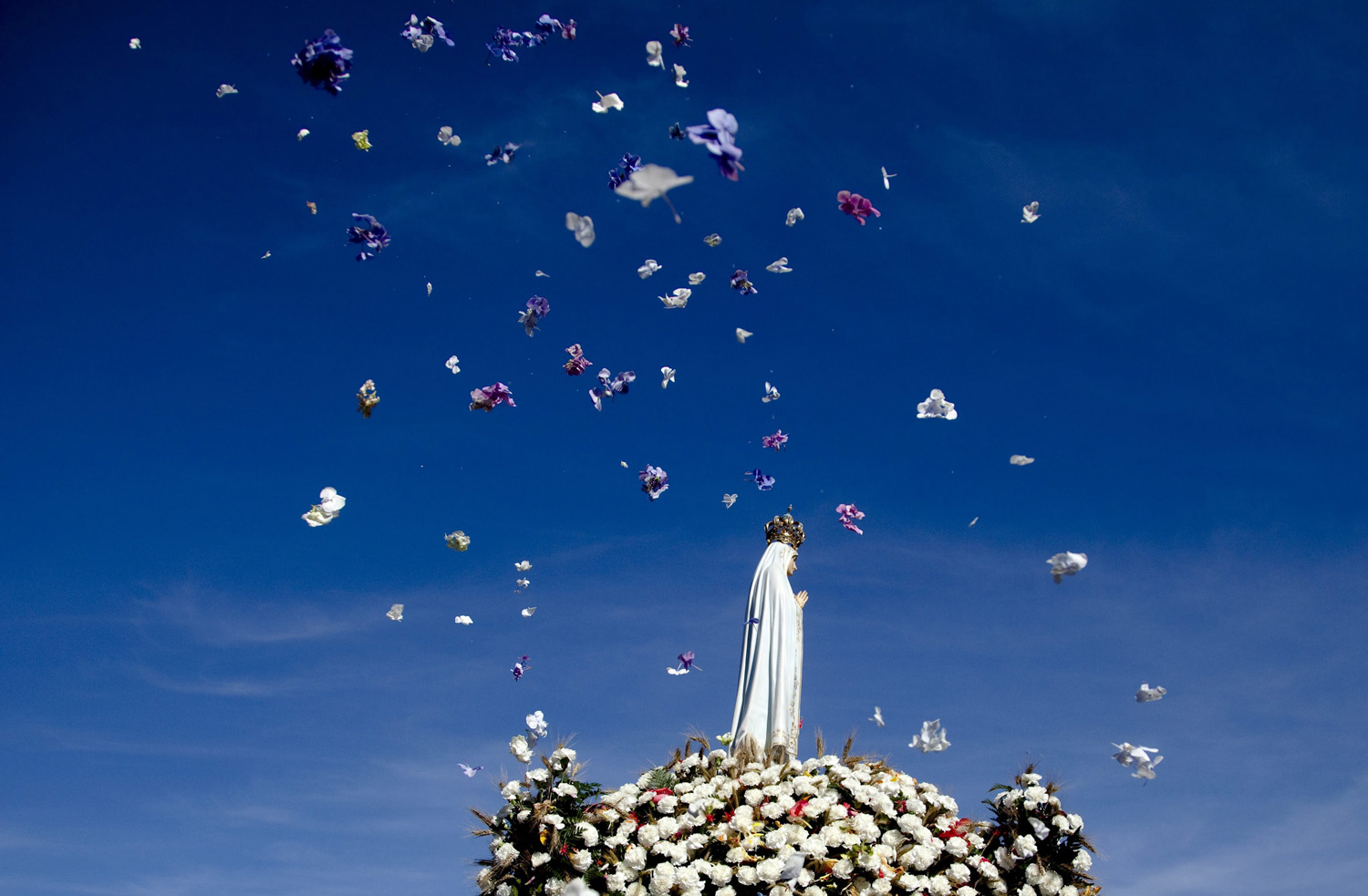 Flowers are thrown in the air as the Image of Our Lady of Fatima is carried over at the Fatima Sanctuary during the pilgrimage at Fatima Sanctuary, in Fatima, Portugal on August 13, 2014.