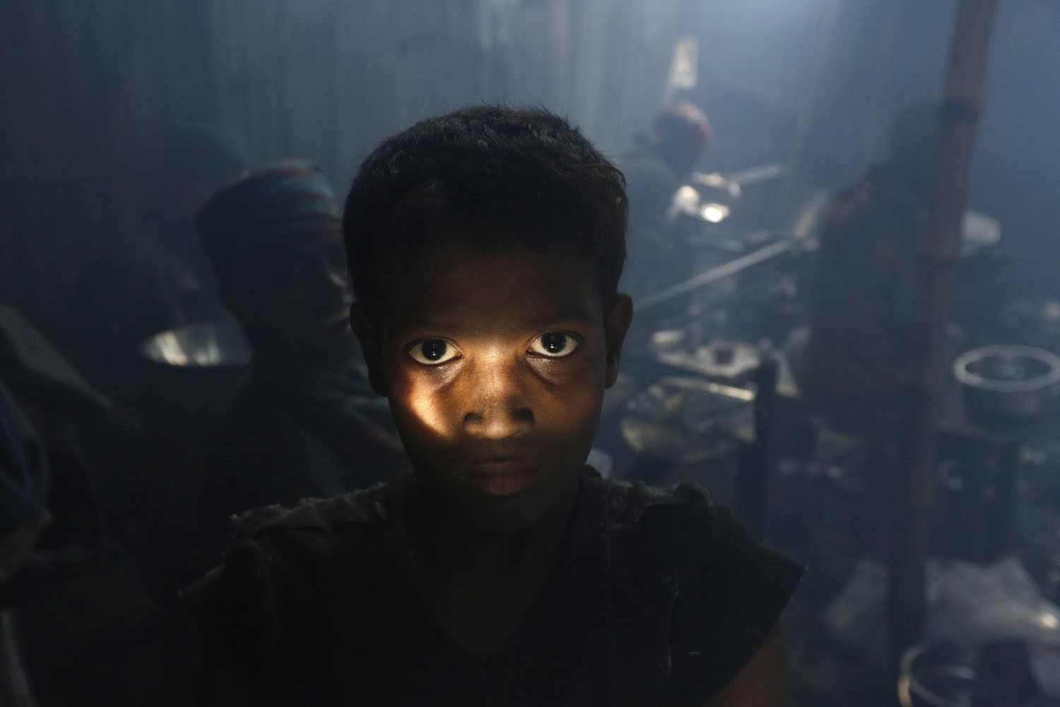 Aug. 25, 2014. A Bangladeshi child worker poses during a break as he makes aluminium bowls at a small factory in Dhaka, Bangladesh. The workers get 2/3 euro per day while they work in unsafe conditions.