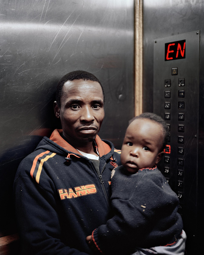 A man and a young boy in an elevator.