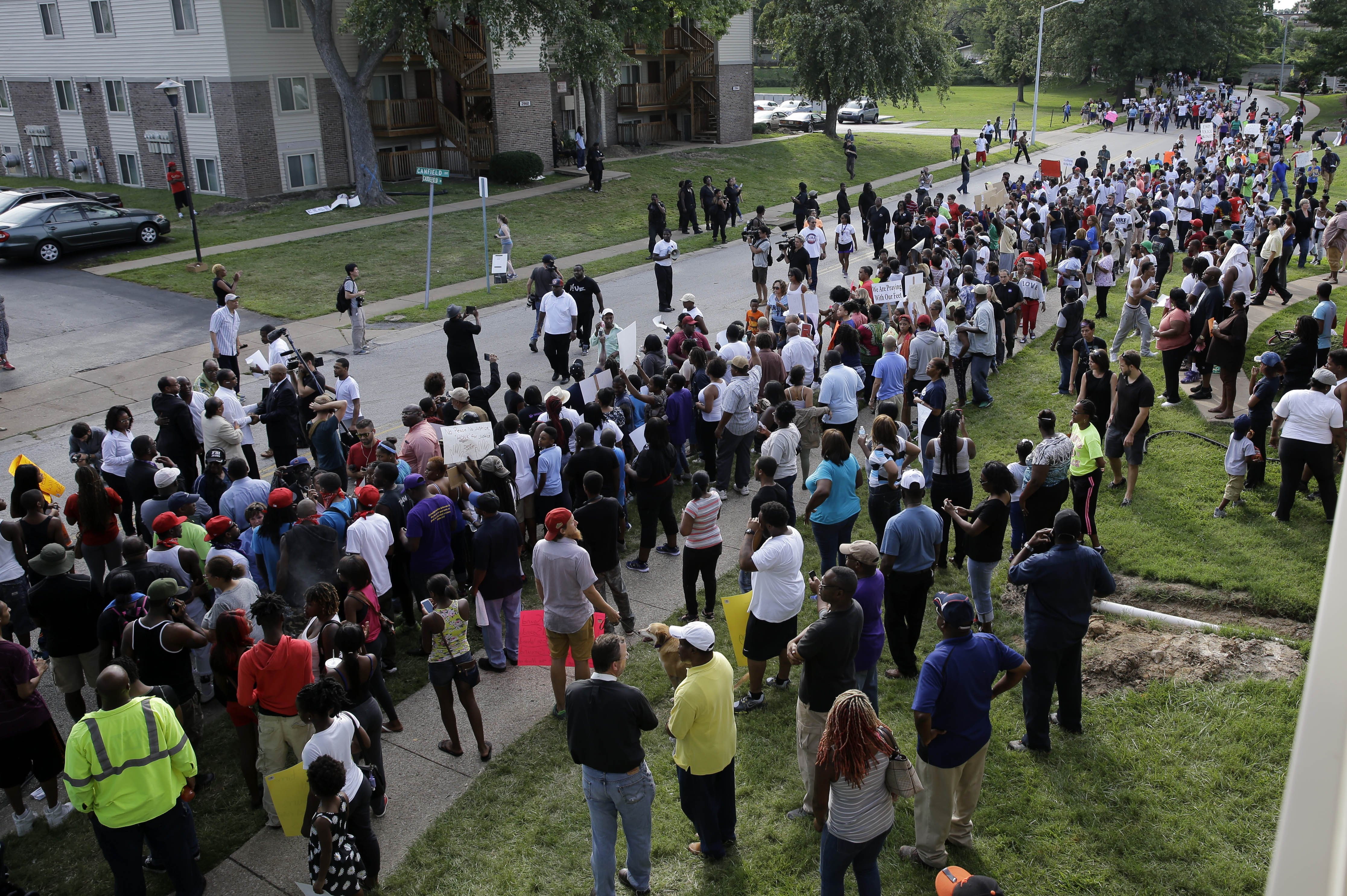 Thousands of demonstrators peacefully march to the spot where Michael Brown was shot and killed by police in Ferguson, Mo. on Aug. 14, 2014.