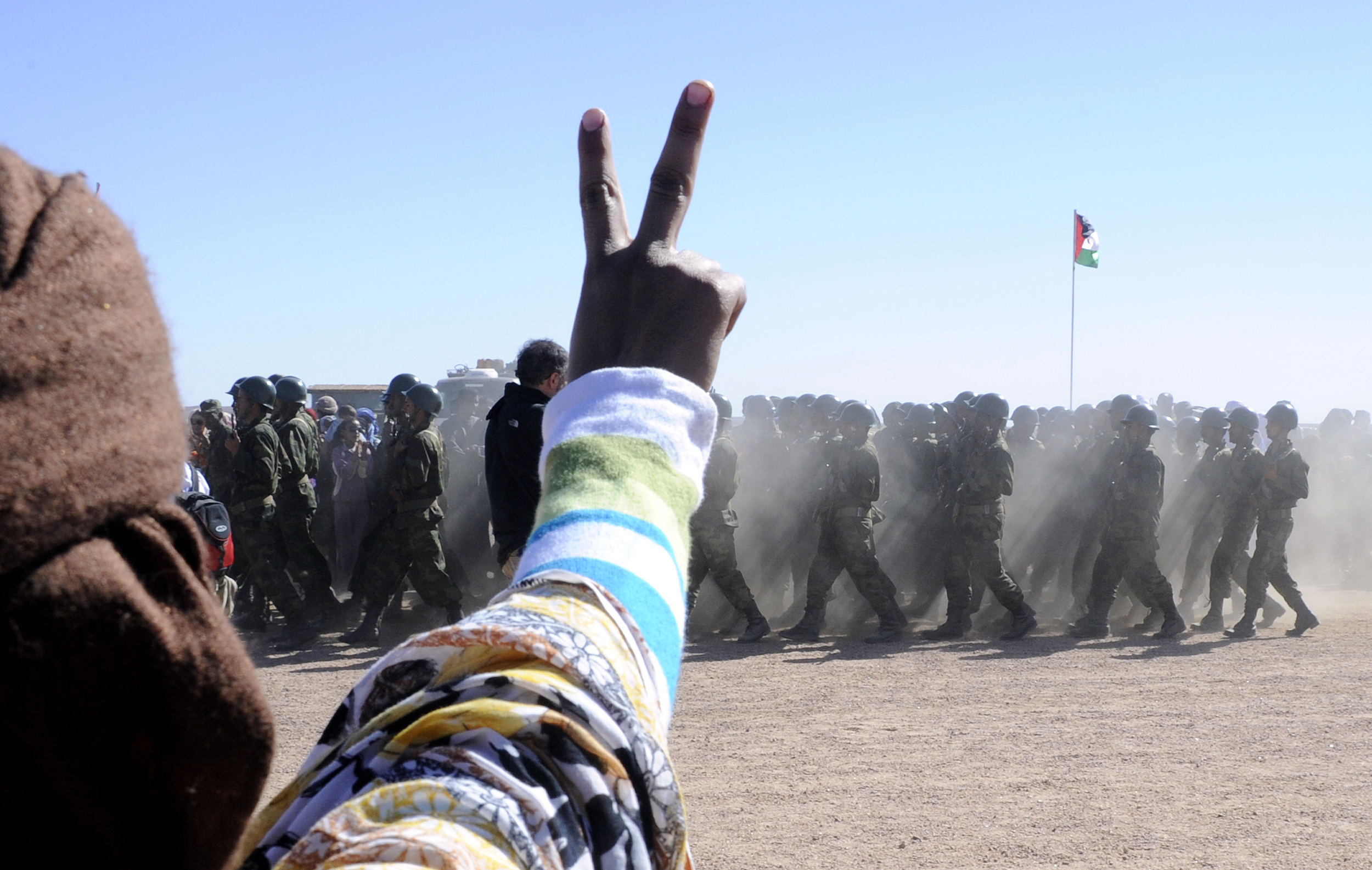 A man flashes a V sign as soldiers from the proindependence Polisario Front parade during a ceremony marking the 35th anniversary of the proclamation of independence of the Sahrawi Arab Democratic Republic in the Western Saharan village of Tifariti on Feb. 27, 2011