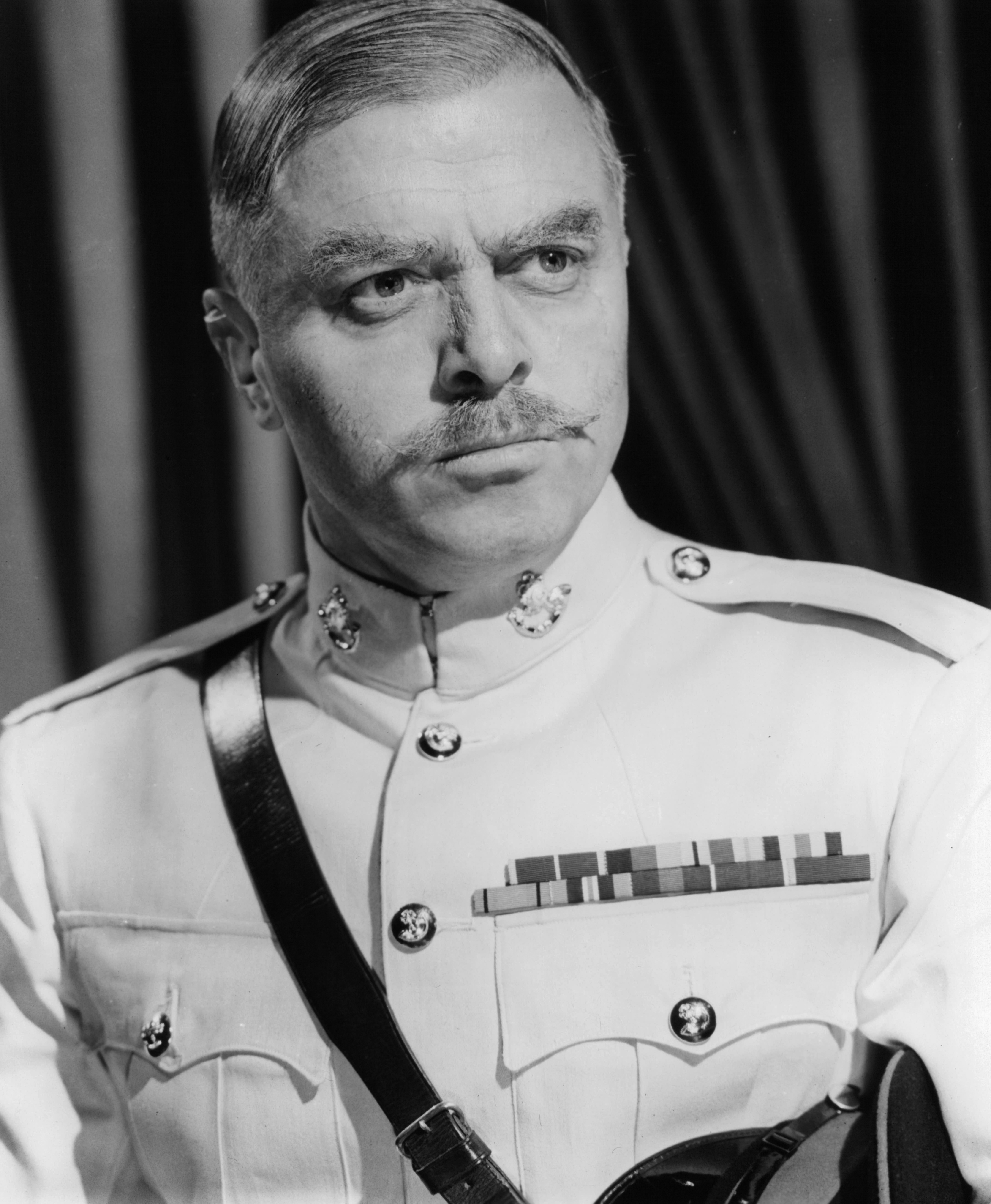 Richard Attenborough standing in uniform in a scene from the film Guns At Batas in 1964.