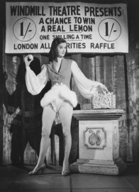 """In the midst of a wartime lemon shortage, a woman """"auctions off"""" a lemon in London, 1944. (The auction was staged by photographer David Scherman.)"""