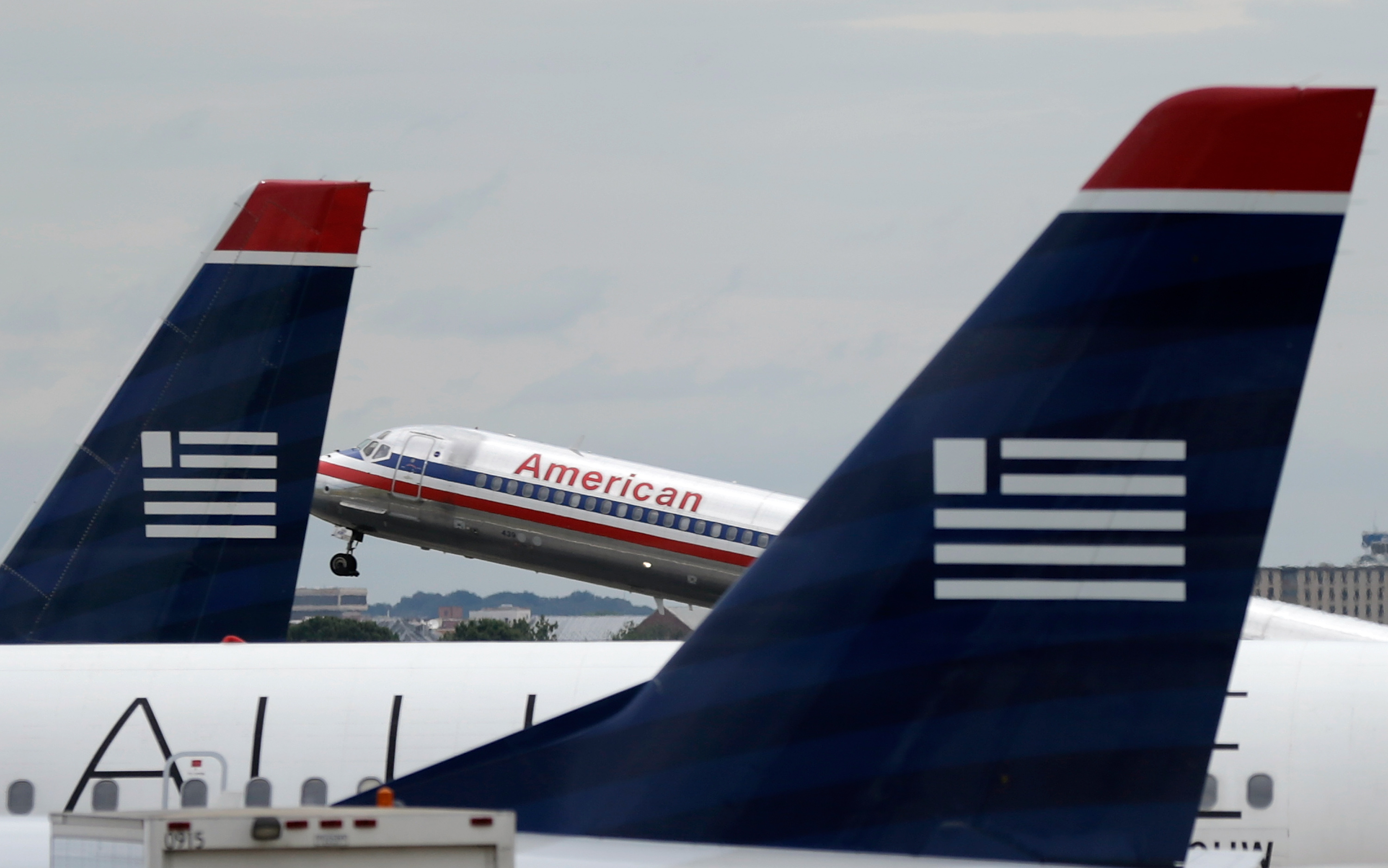 An American Airlines jet takes off behind US Airways jets at Ronald Reagan Washington National Airport August 13, 2013 in Arlington, Virginia.