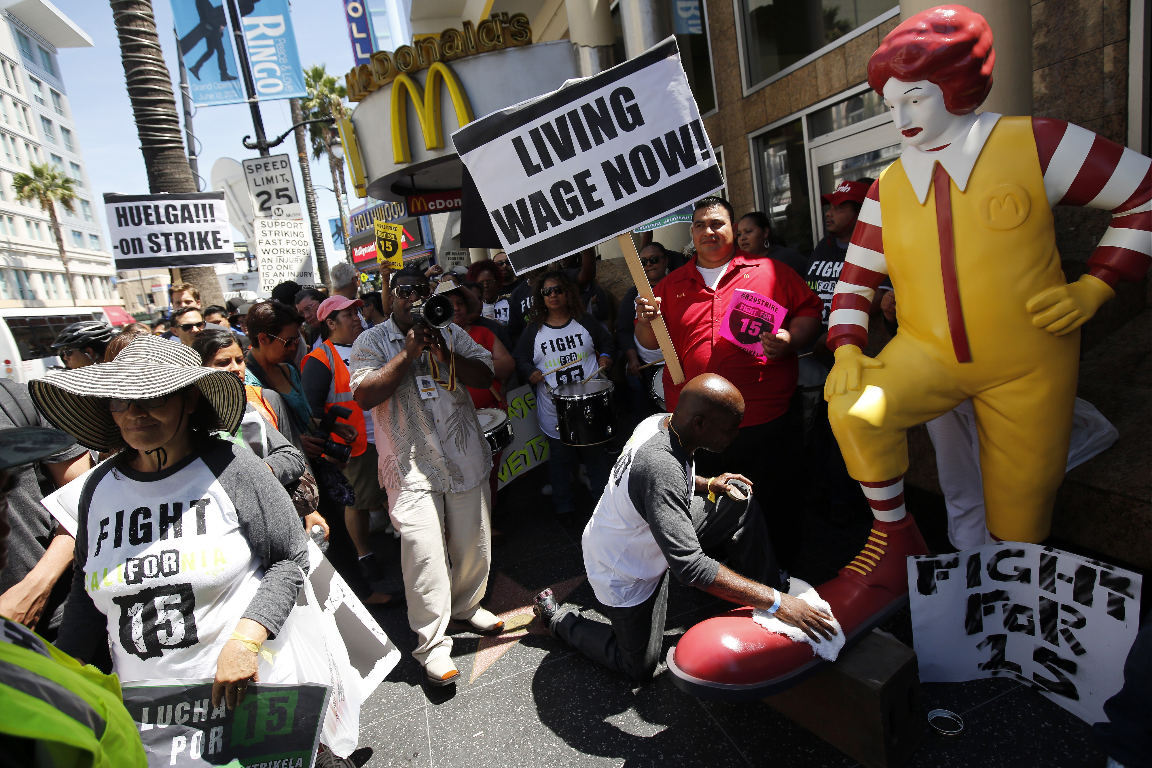 Robert Wideman, a maintenance mechanic at McDonalds Corp., shines the shoes of a Ronald McDonald statue outside of a restaurant while protesting with fast-food workers and supporters organized by the Service Employees International Union (SEIU) in Los Angeles, California, U.S., on Thursday, Aug. 29, 2013.