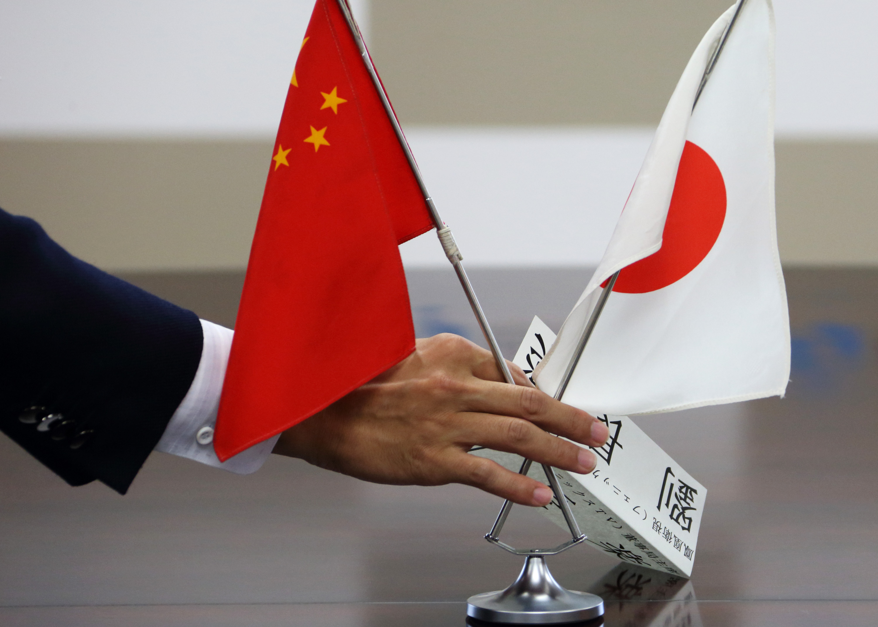 A staff member of Japan's Ministry of Economy, Trade and Industry arranges Chinese and Japanese flags before a meeting with a group of Chinese business leaders in Tokyo on Sept. 26, 2013