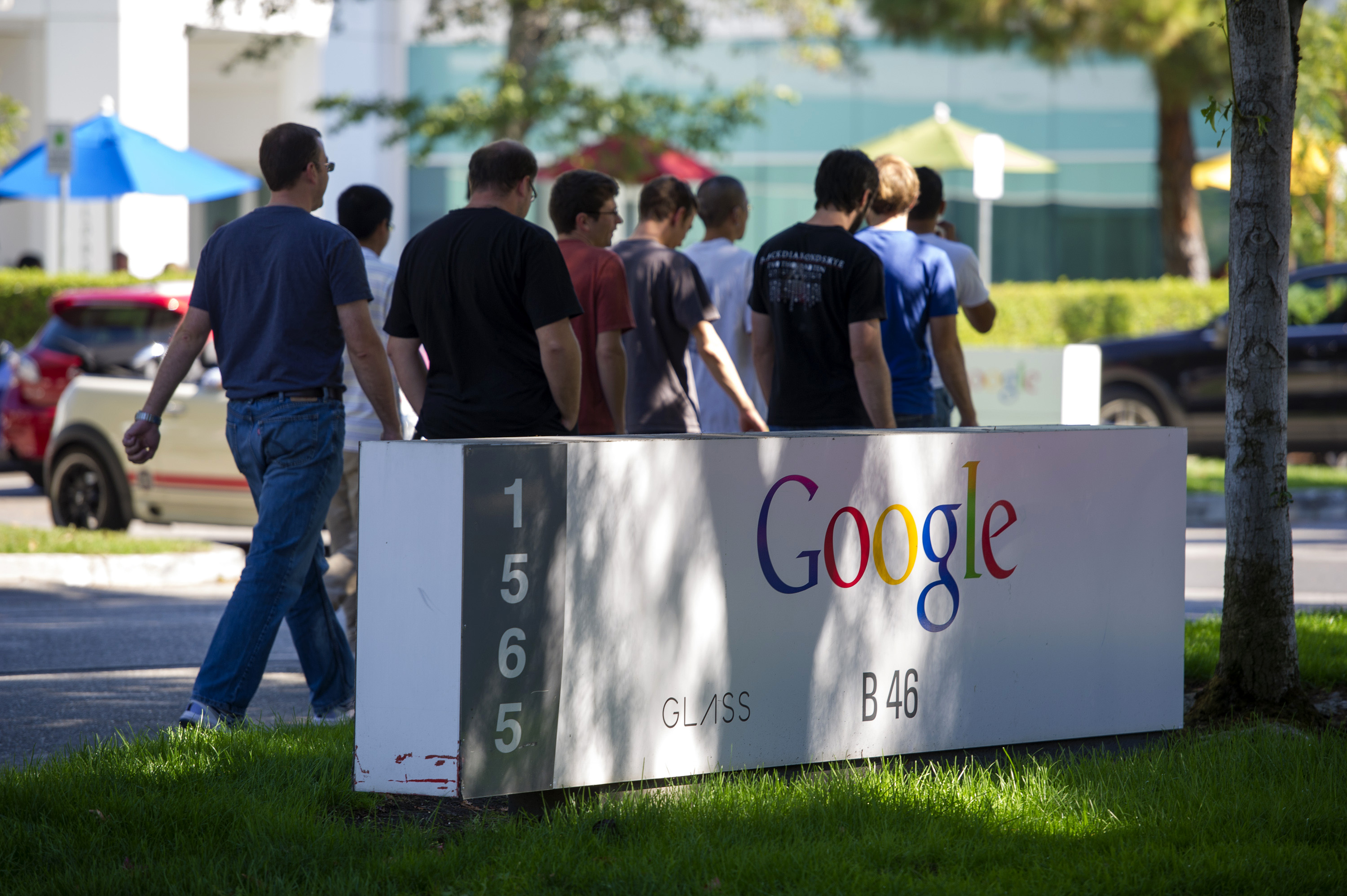 Pedestrians walk past Google Inc. signage displayed in front of the company's headquarters in Mountain View, California, U.S., on Friday, Sept. 27, 2013.