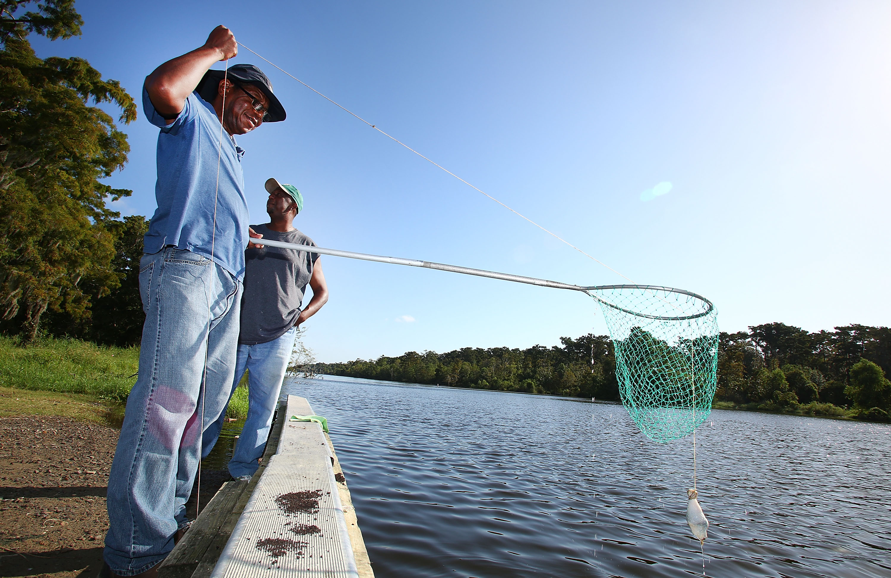 Mike Coleman and Jarad Williams check their crab traps on October 4, 2013 in Grand Isle, Louisiana.