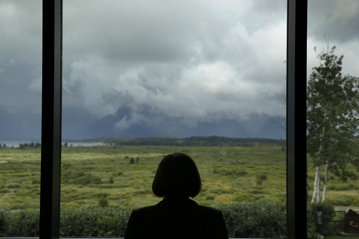 Aug. 23, 2014. Jill Vardy, of the Bank of Canada, looks out at the Teton Range during a break at the Jackson Hole Economic Policy Symposium at the Jackson Lake Lodge in Grand Teton National Park near Jackson, Wyo.