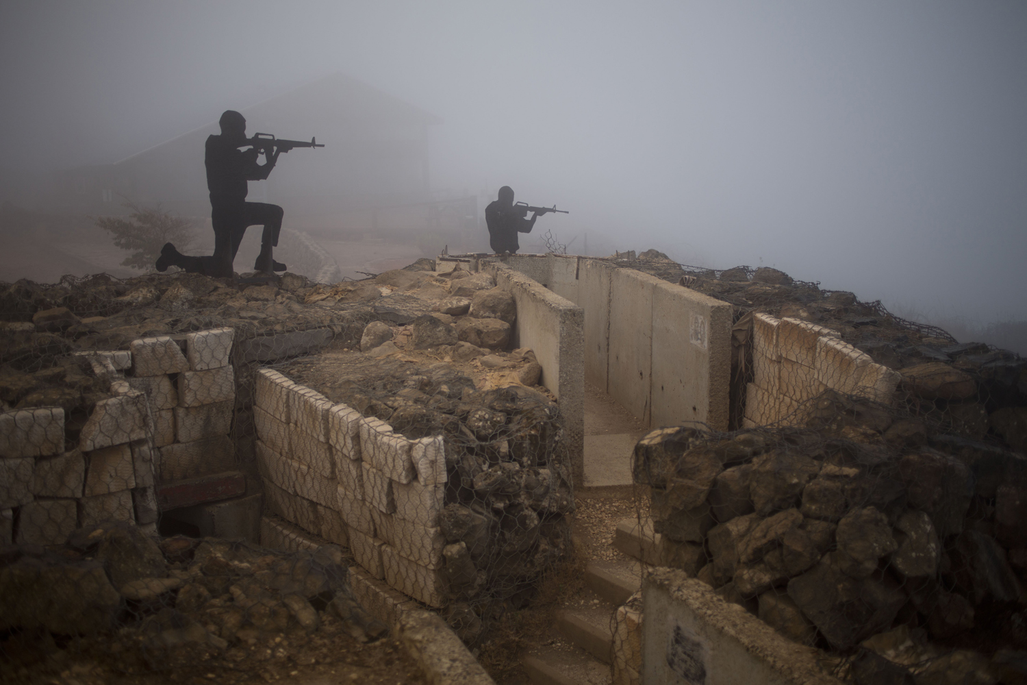 Aug. 29, 2014. Metal boards in the shape of gunmen sit on an old bunker at an observation point on Mt. Bental in the Israeli controlled Golan Heights, overlooking the border with Syria near the Quneitra province.