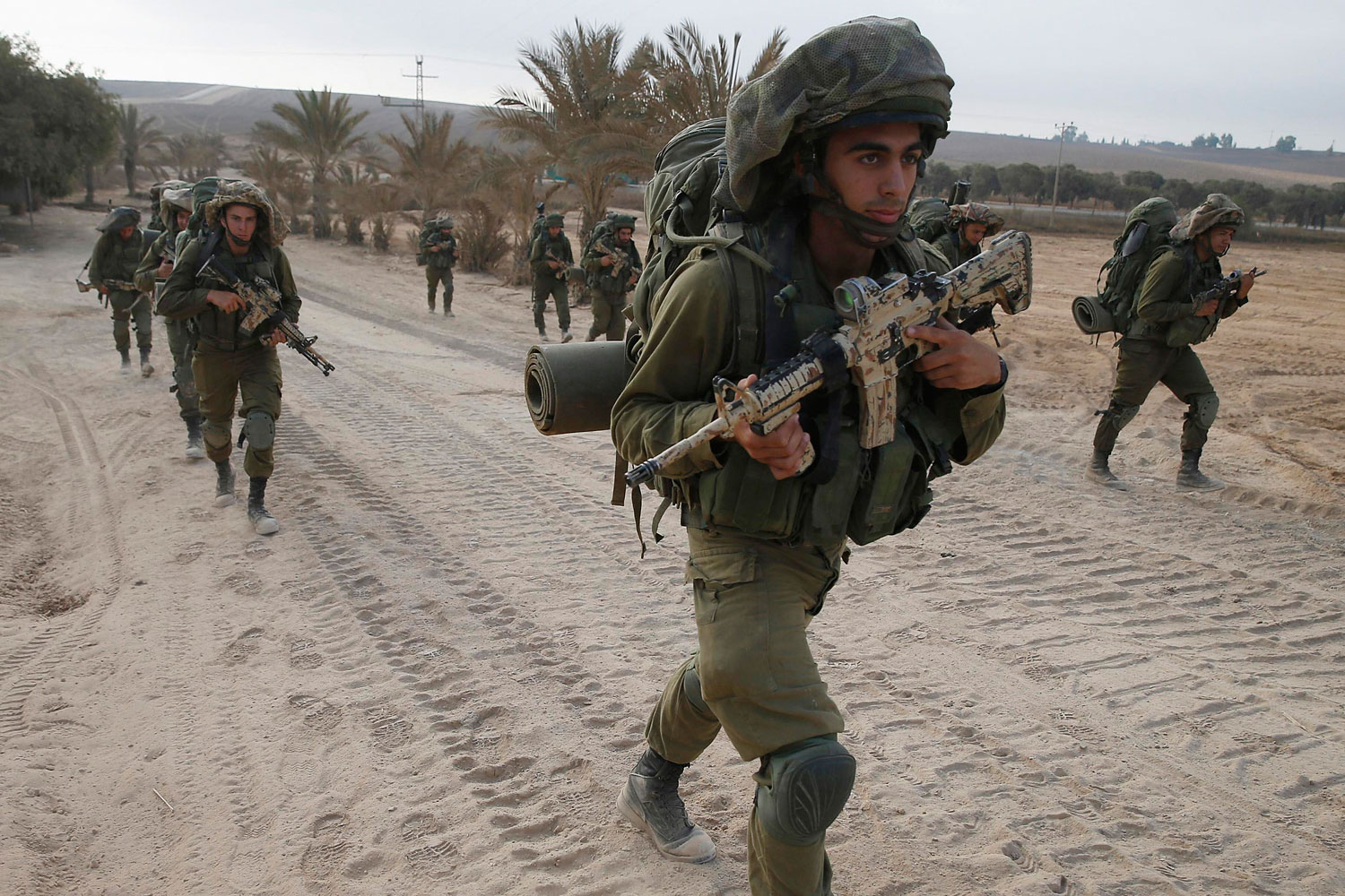Israeli soldiers walk outside the Gaza Strip as they proceed towards Gaza August 2, 2014.