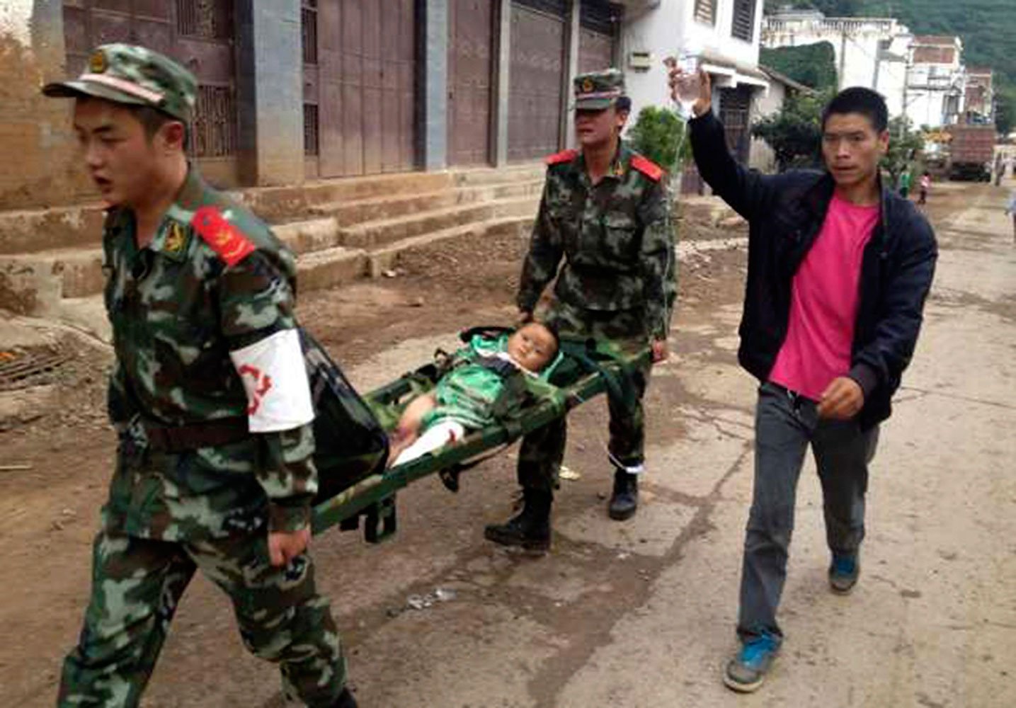 Paramilitary policemen carry an injured child on a stretcher as they carry out rescue operations after an earthquake hit Longtoushan township of Ludian county, Yunnan province Aug. 3, 2014.