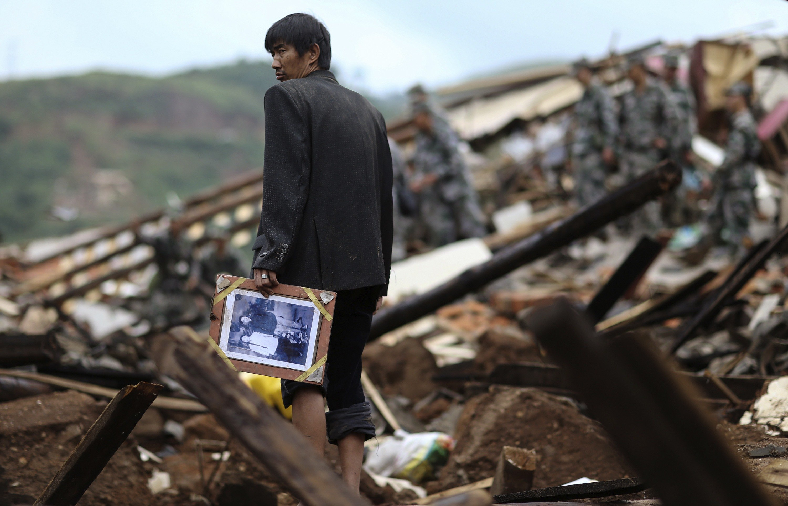 Aug. 4, 2014. A man holds a picture as he stands among debris of collapsed buildings after an earthquake hit Longtoushan township of Ludian county, Yunnan province.