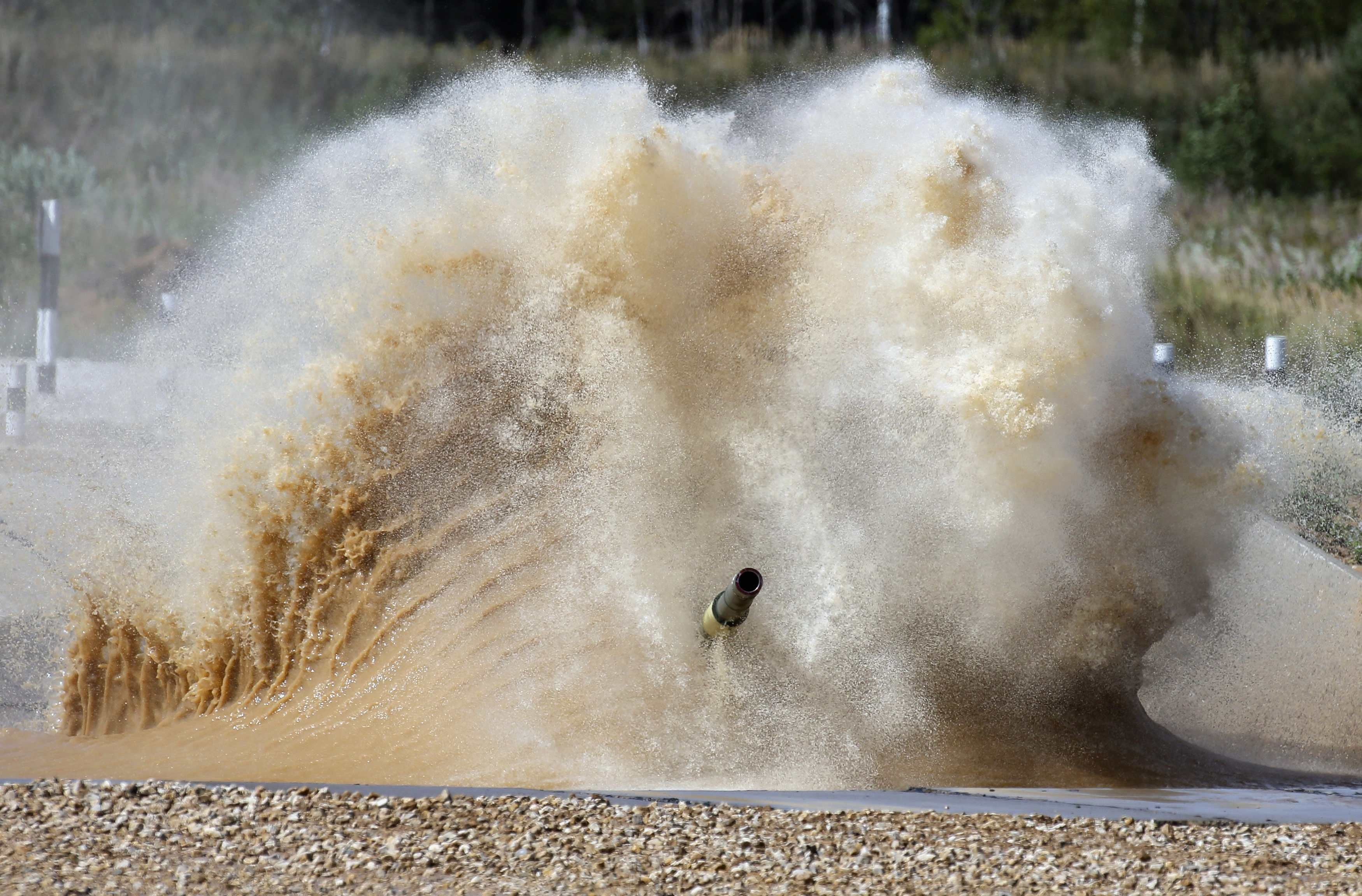 Aug. 4, 2014. A tank drives through a water obstacle on the course of the Tank Biathlon world championship in Alabino outside Moscow.
