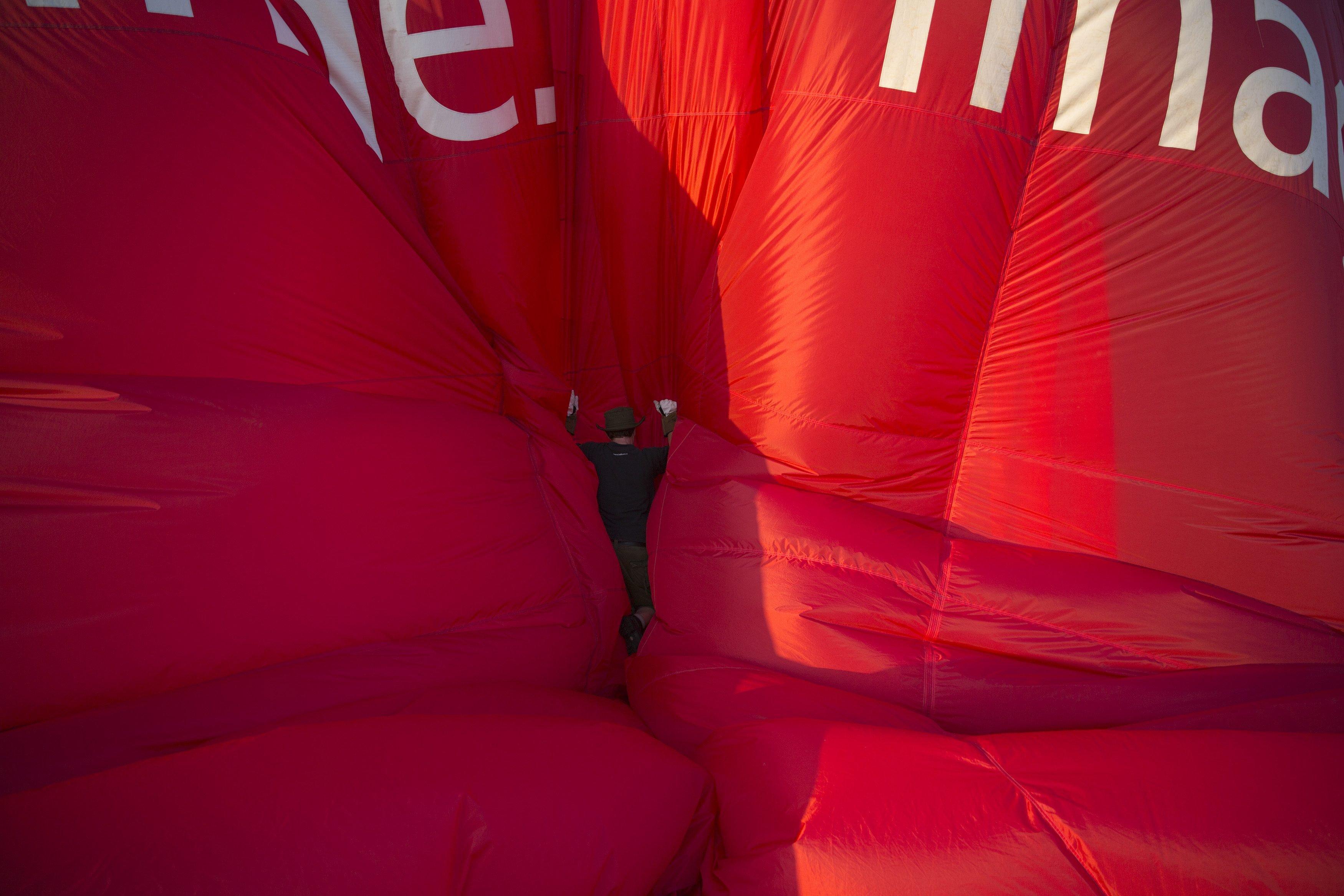 Aug. 7, 2014. A balloonist checks a balloon as it is deflated at the International Balloon Fiesta near Bristol in western England.