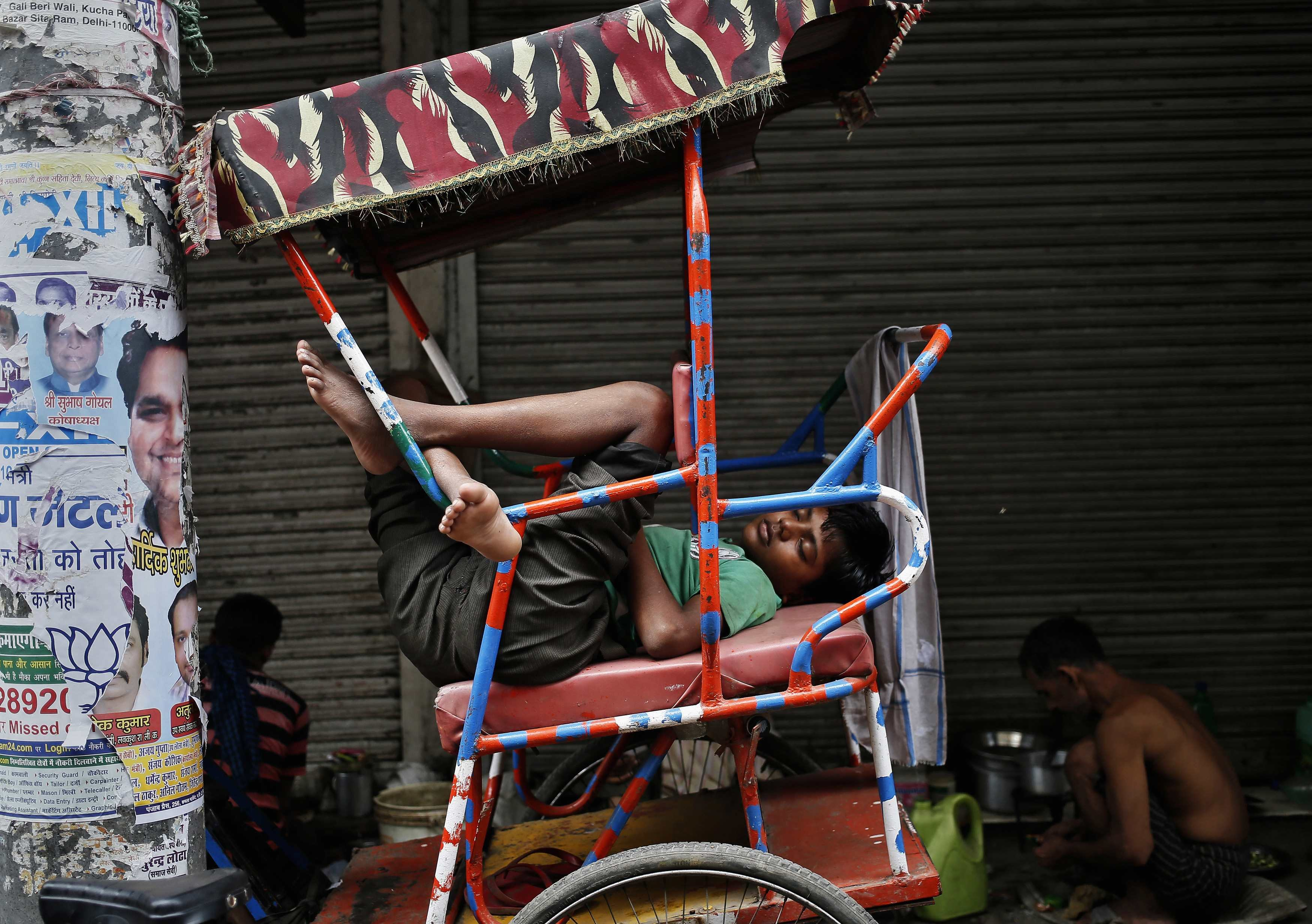Aug. 8, 2014. A man takes a nap on a cycle rickshaw along a roadside in the old quarters of Delhi.
