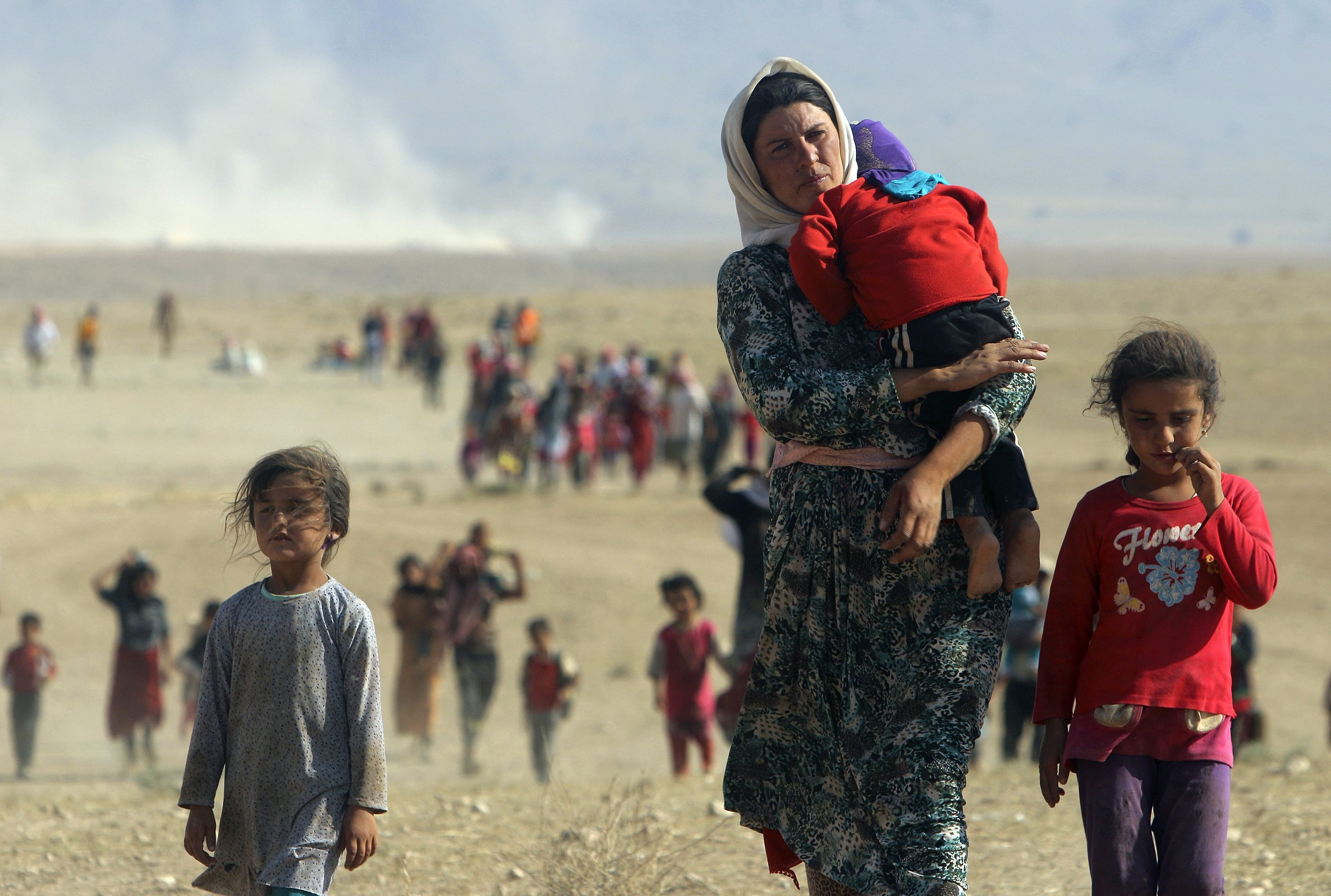 Displaced people from the minority Yazidi sect, fleeing violence from forces loyal to the Islamic State in Sinjar town, walk towards the Syrian border, on the outskirts of Sinjar mountain, near the Syrian border town of Elierbeh of Al-Hasakah Governorate on August 11, 2014.