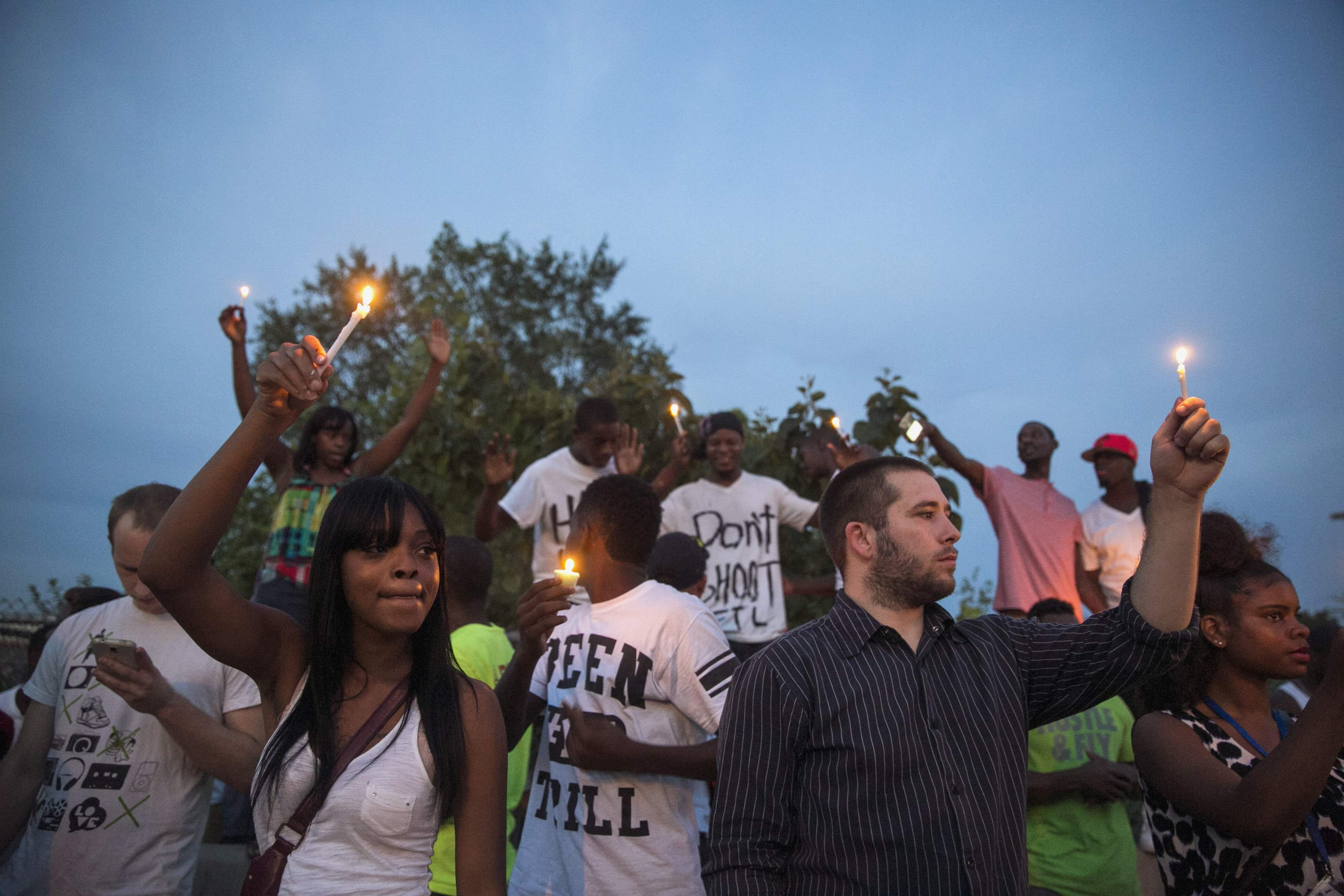 Protesters light candles as they take part in a peaceful demonstration in Ferguson, Mo. on Aug. 14, 2014.