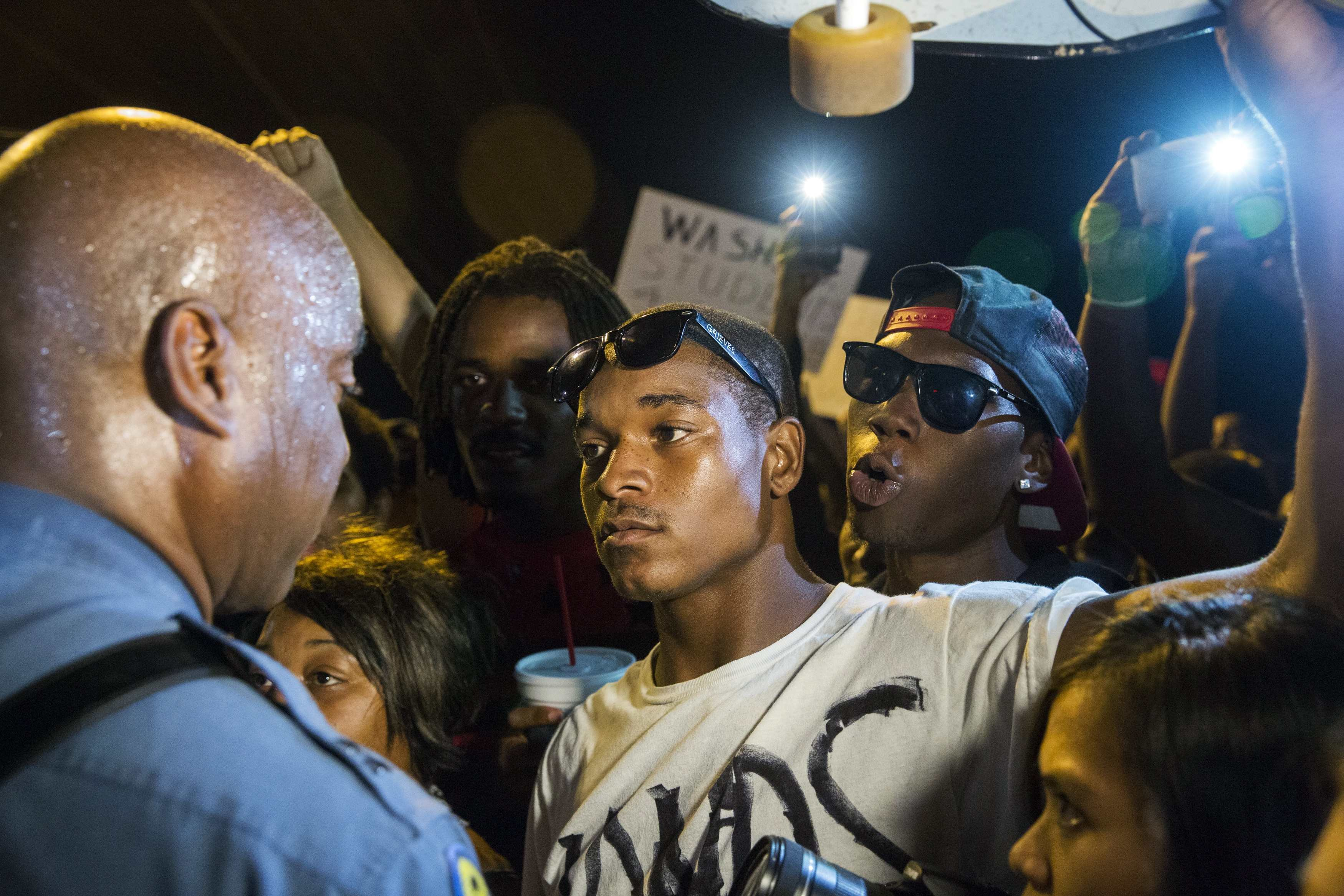 Missouri State Highway Patrol Captain Ron Johnson (L) speaks to protesters as he walks through a peaceful demonstration as communities continue to react to the shooting of Michael Brown in Ferguson, Mo. on Aug. 14, 2014.