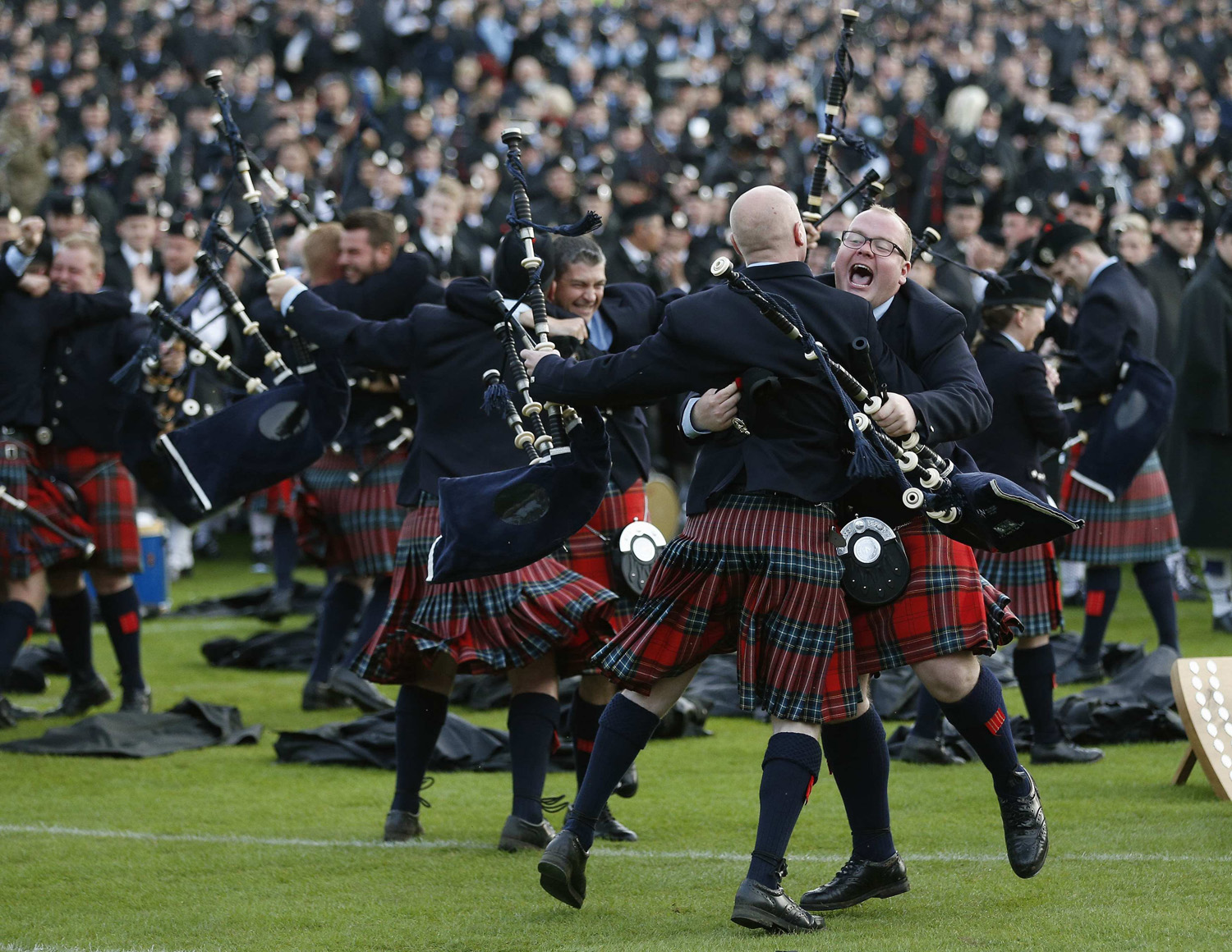Members of the Field Marshall Montgomery Pipe Band react to winning the annual World Pipe Band Championships at Glasgow Green, Scotland on Aug. 16, 2014.