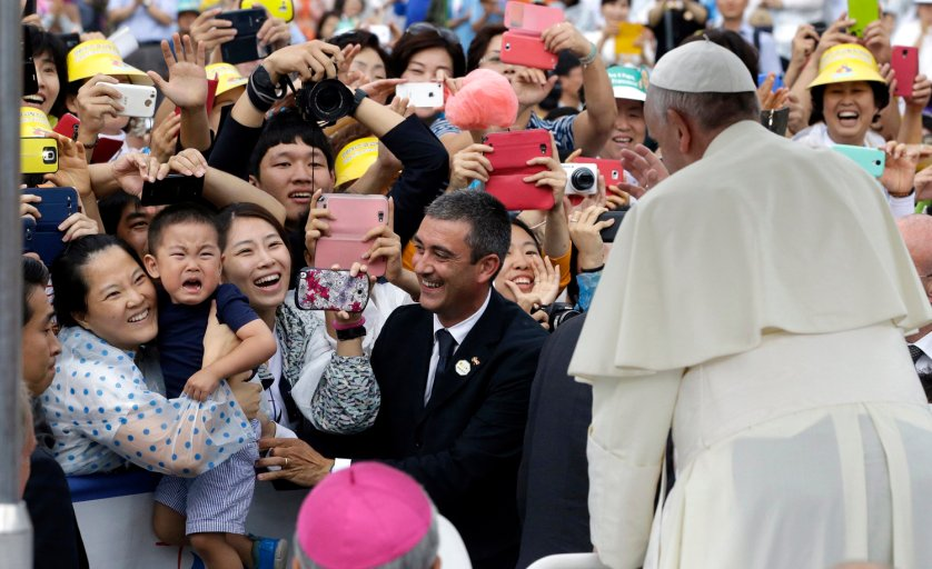 Pope Francis blesses a crying child who does not want to be separated from his mother to be blessed by the pope, as a Vatican gendarmerie (C) smiles, at the pope's arrival for a closing Holy Mass of the 6th Asian Youth Day at Haemi Castle in Haemi, Seoul on Aug. 17, 2014.