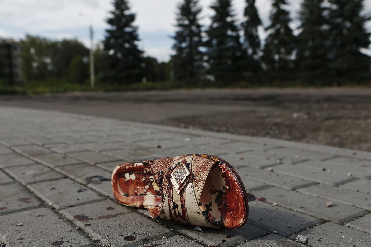 Aug. 19, 2014. A slipper lies near bloodstains on a street after recent shelling in the settlement of Makiivka, on the outskirts of Donetsk.
