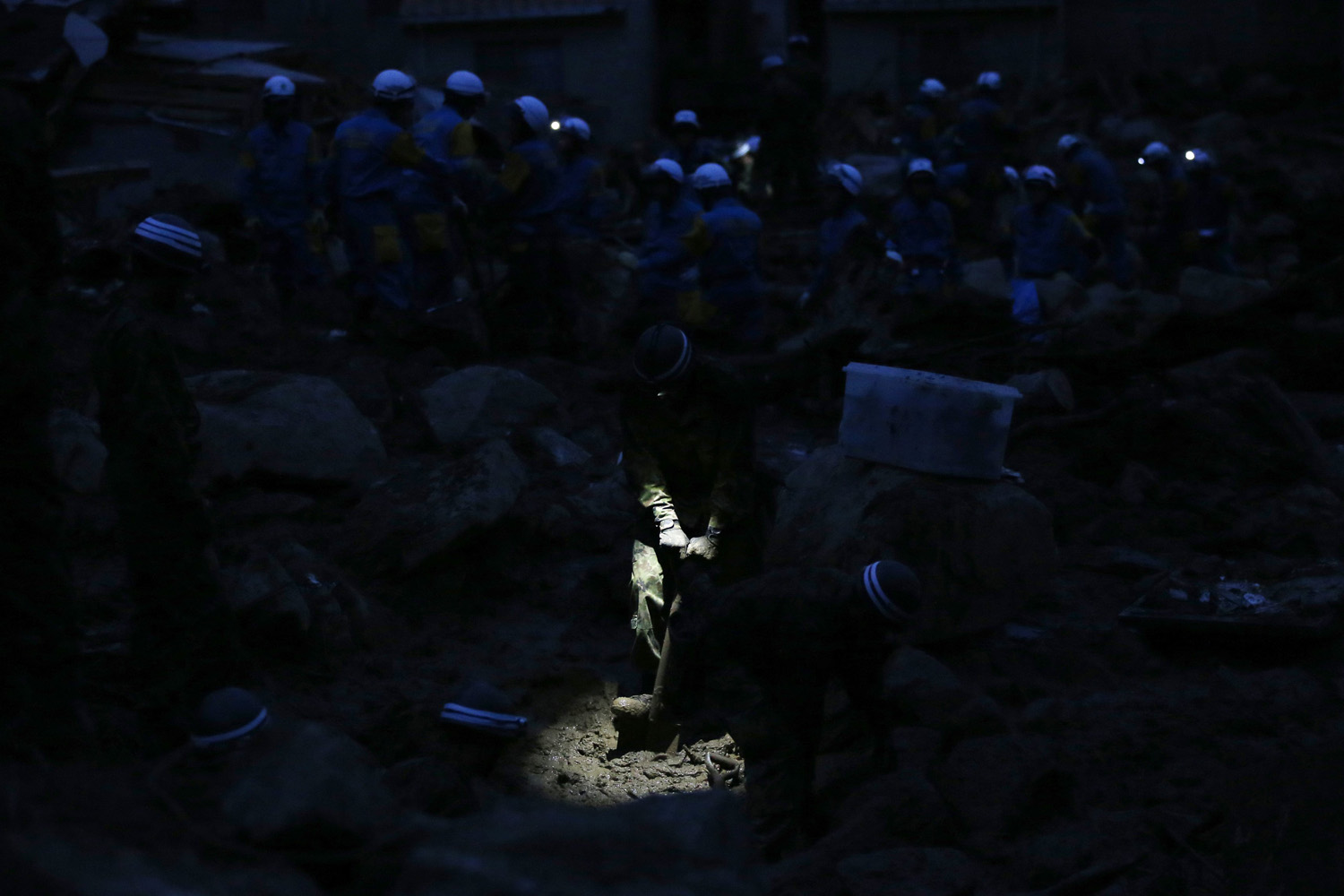 Aug. 21, 2014. A Japan Self-Defense Force (JSDF) soldier searches for survivors at dusk at a site where a landslide swept through a residential area at Asaminami ward in Hiroshima, western Japan.