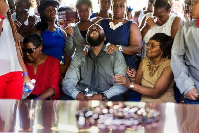 Michael Brown Sr. yells out as his son's casket is lowered into the ground at St. Peter's Cemetery in St. Louis
