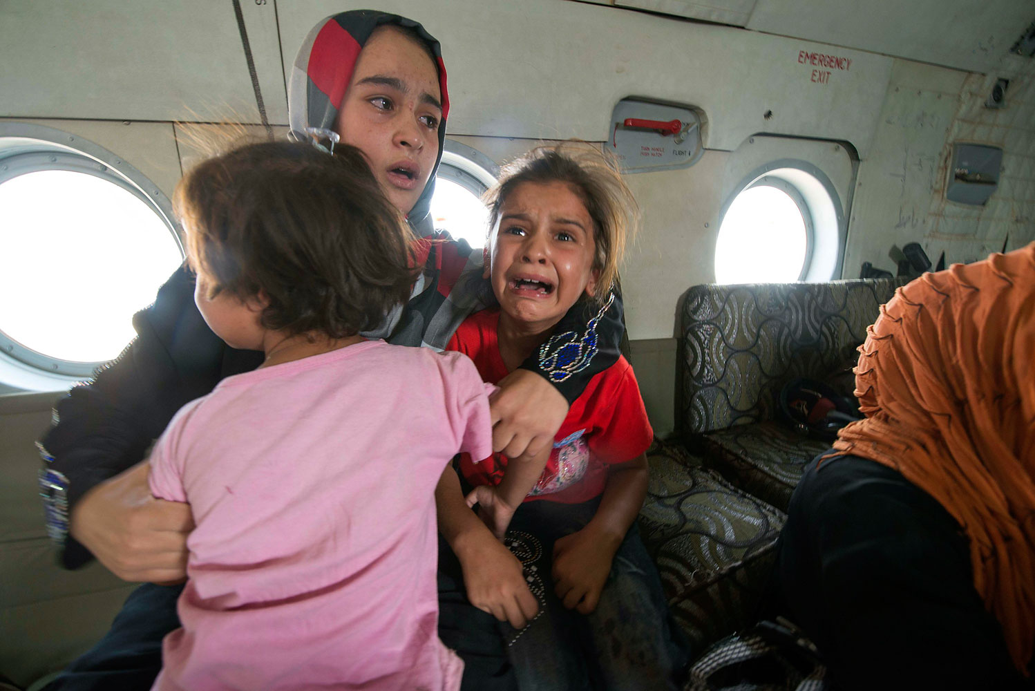 A woman and children react in a military helicopter after being evacuated by Iraqi forces from Amerli, north of Baghdad, Aug. 29, 2014.