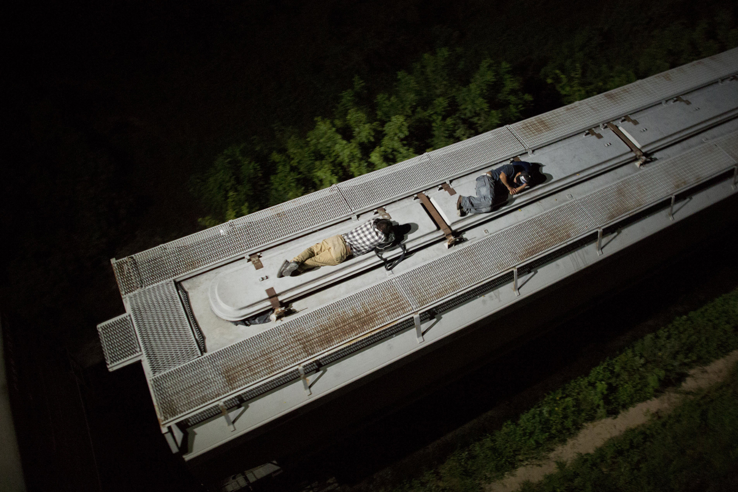 Aug. 26, 2014. Central American migrants sleep atop a moving freight train as it heads north from Arriaga toward Chahuites, Mexico.