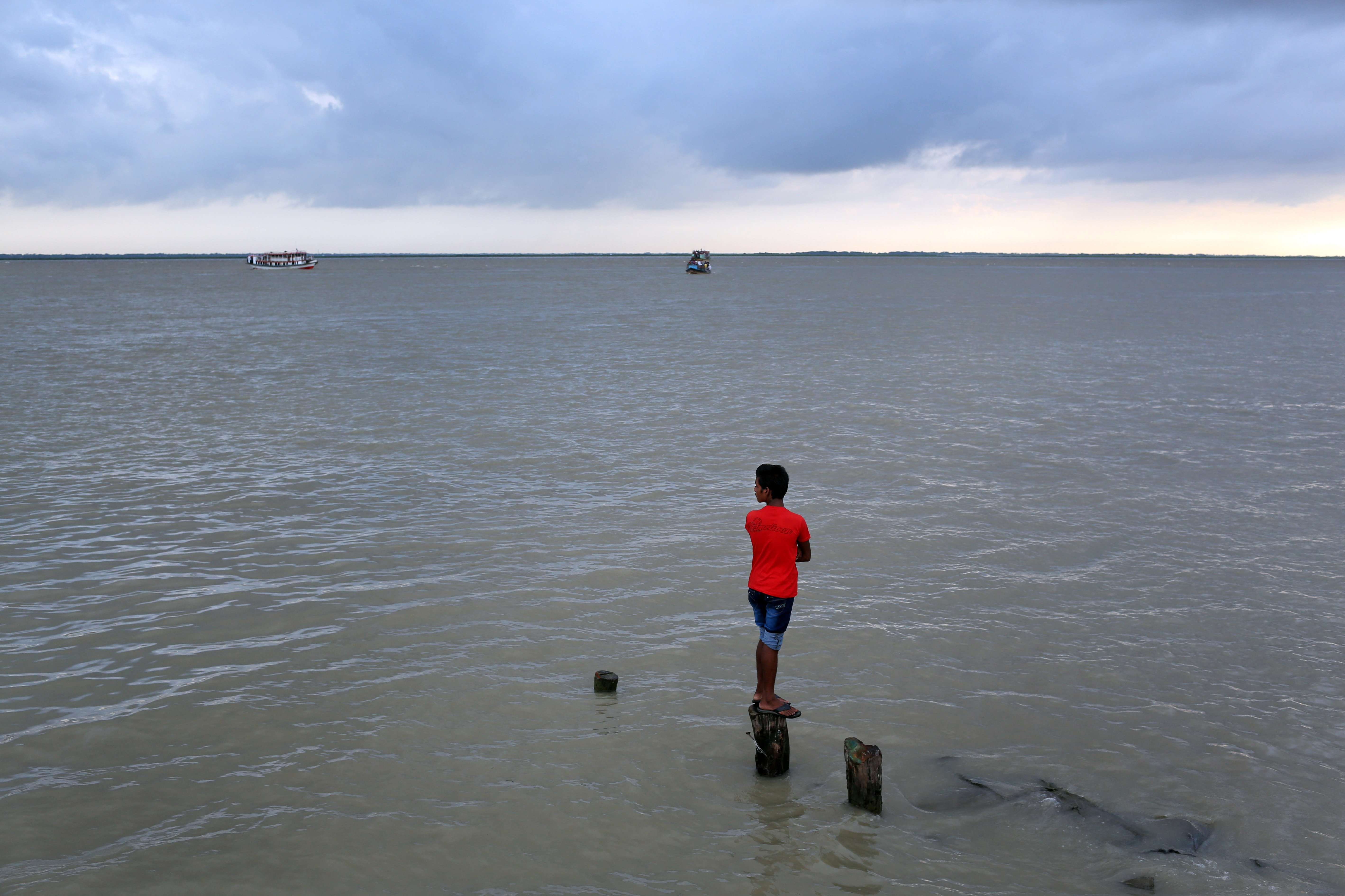Aug. 4, 2014. A Bangladeshi boy watches as rescuers search the River Padma after a passenger ferry capsized in Munshiganj district, Bangladesh.