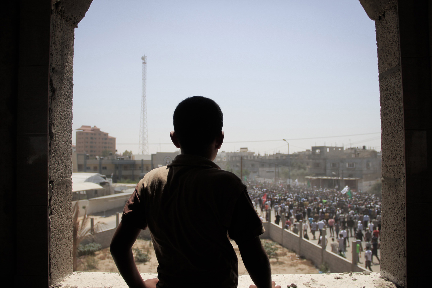 Aug. 21, 2014. A young Palestinian boy watches people gathering for the funeral of three top senior Hamas commanders, Mohammed Abu Shamala, Mohammed Barhoum and Raed al-Attar, all three are believed to have died overnight in ongoing Israeli airstrikes on Rafah.