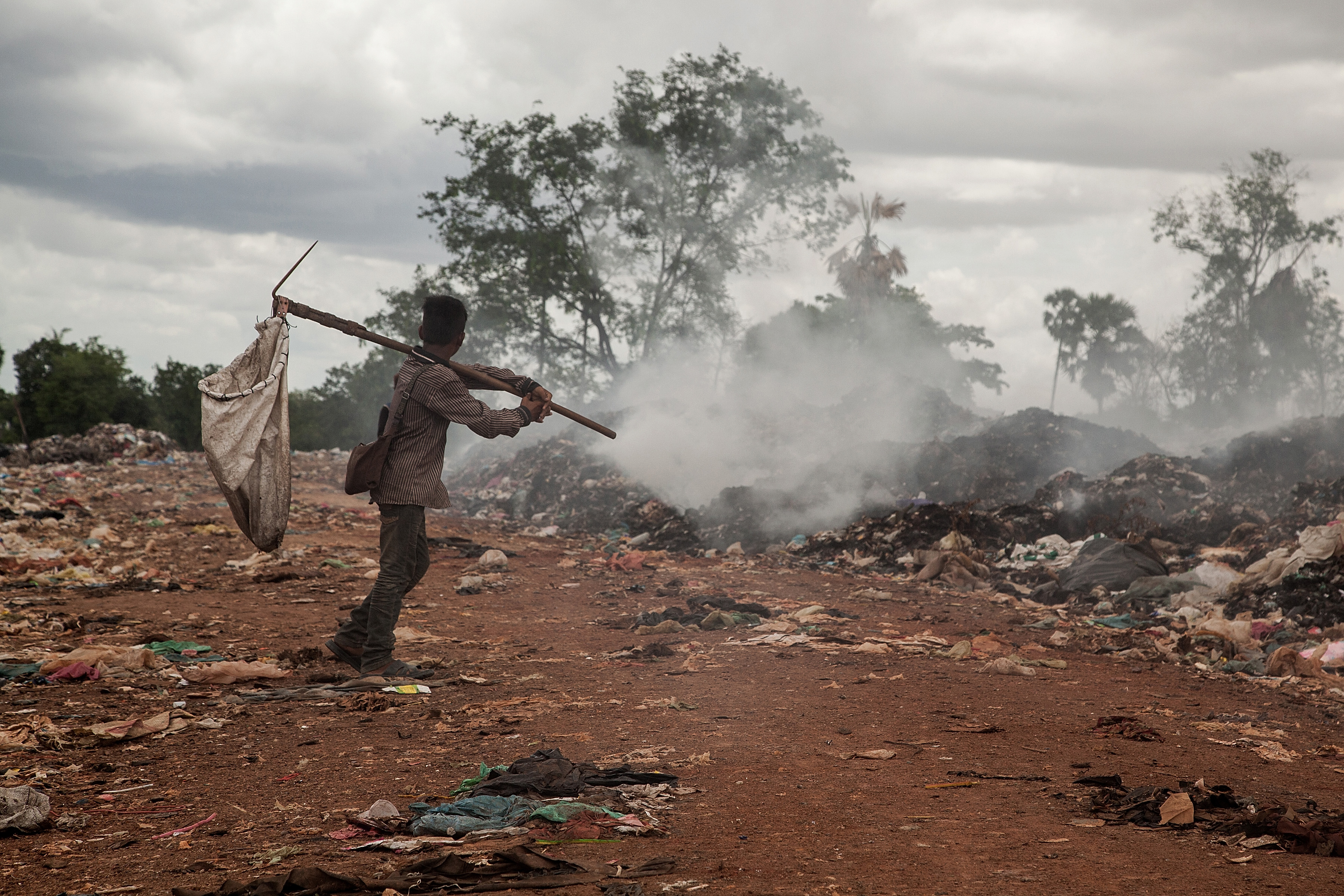 A young scavenger walks near a burning pile of trash in the Anlong Pi landfill on June 11, 2014 in Siem Reap, Cambodia.