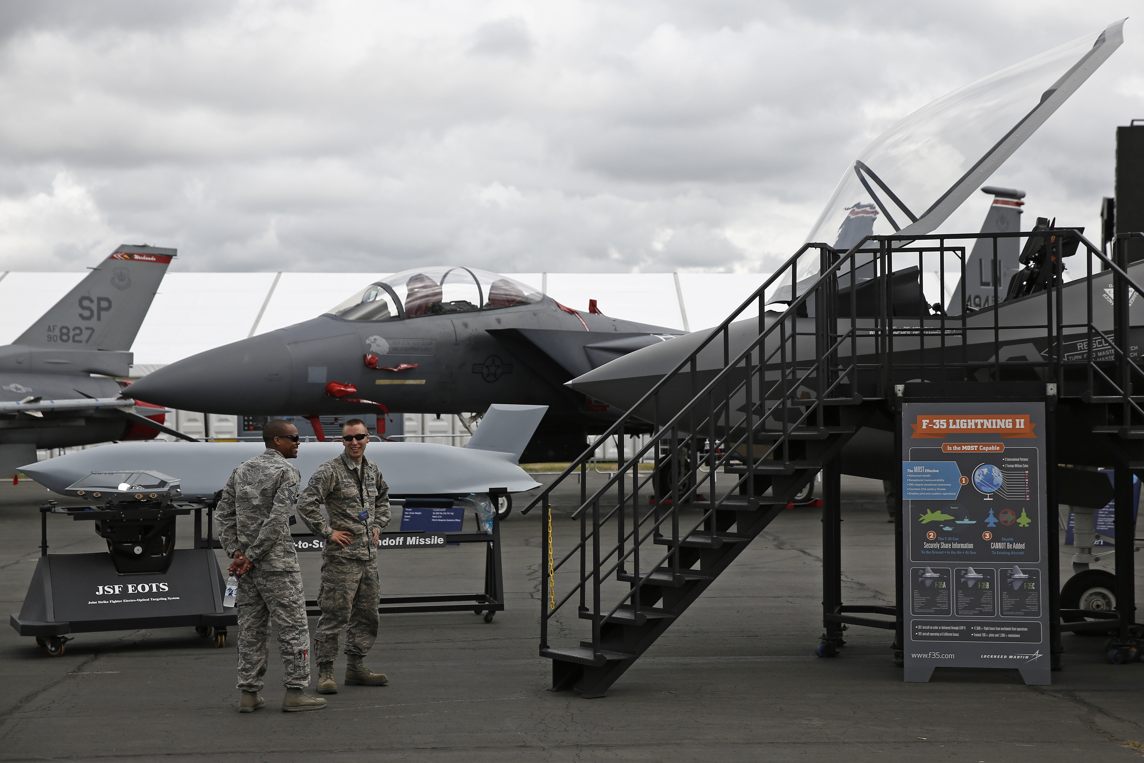 Military personnel talk as they stand beside an F-15E Strike Eagle fighter jet, left, prior to the opening of the Farnborough International Airshow in Farnborough, U.K., on Sunday, July 13, 2014.