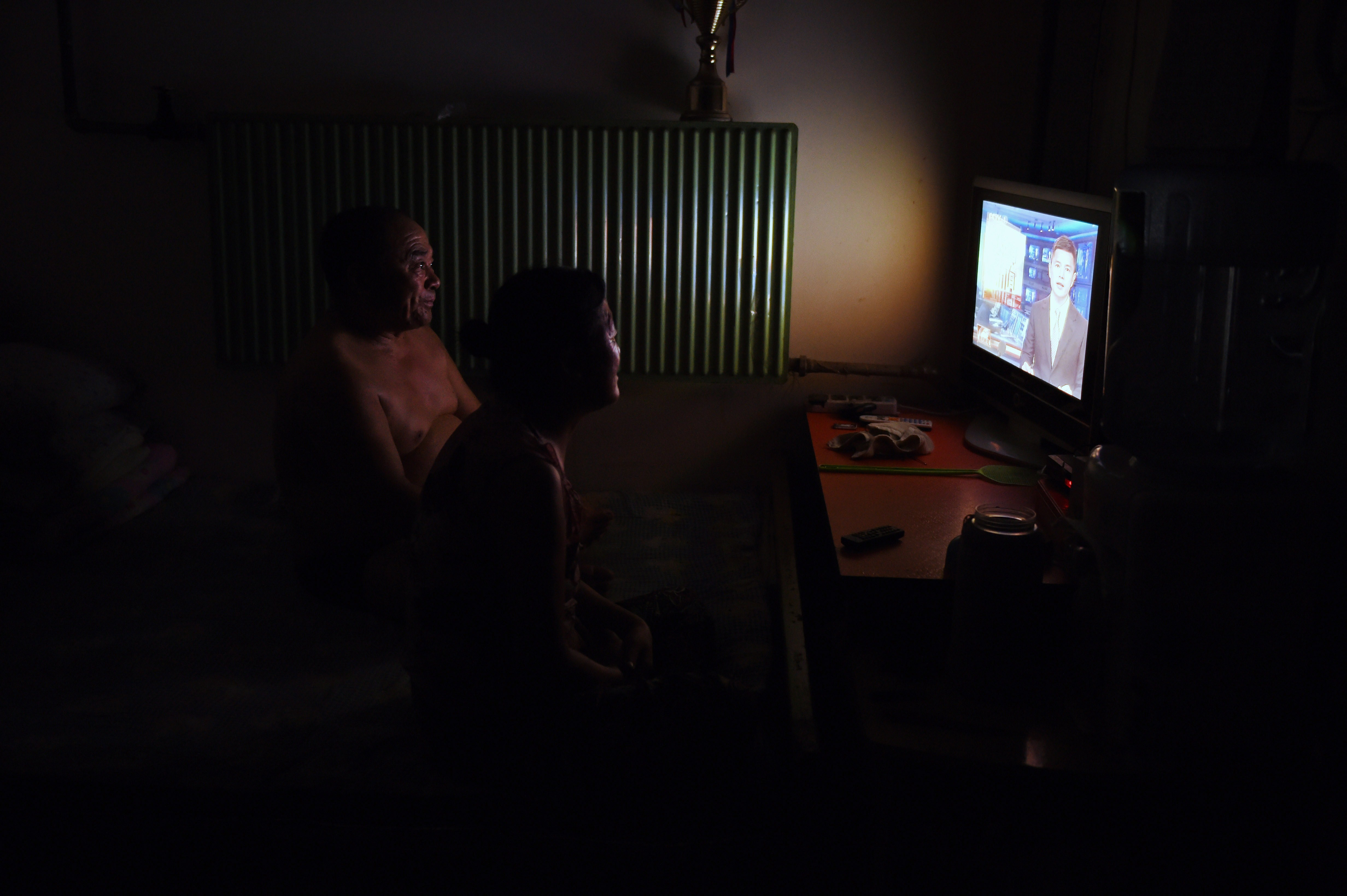 This photo taken on July 15, 2014 shows a couple watching TV in their apartment in Beijing.