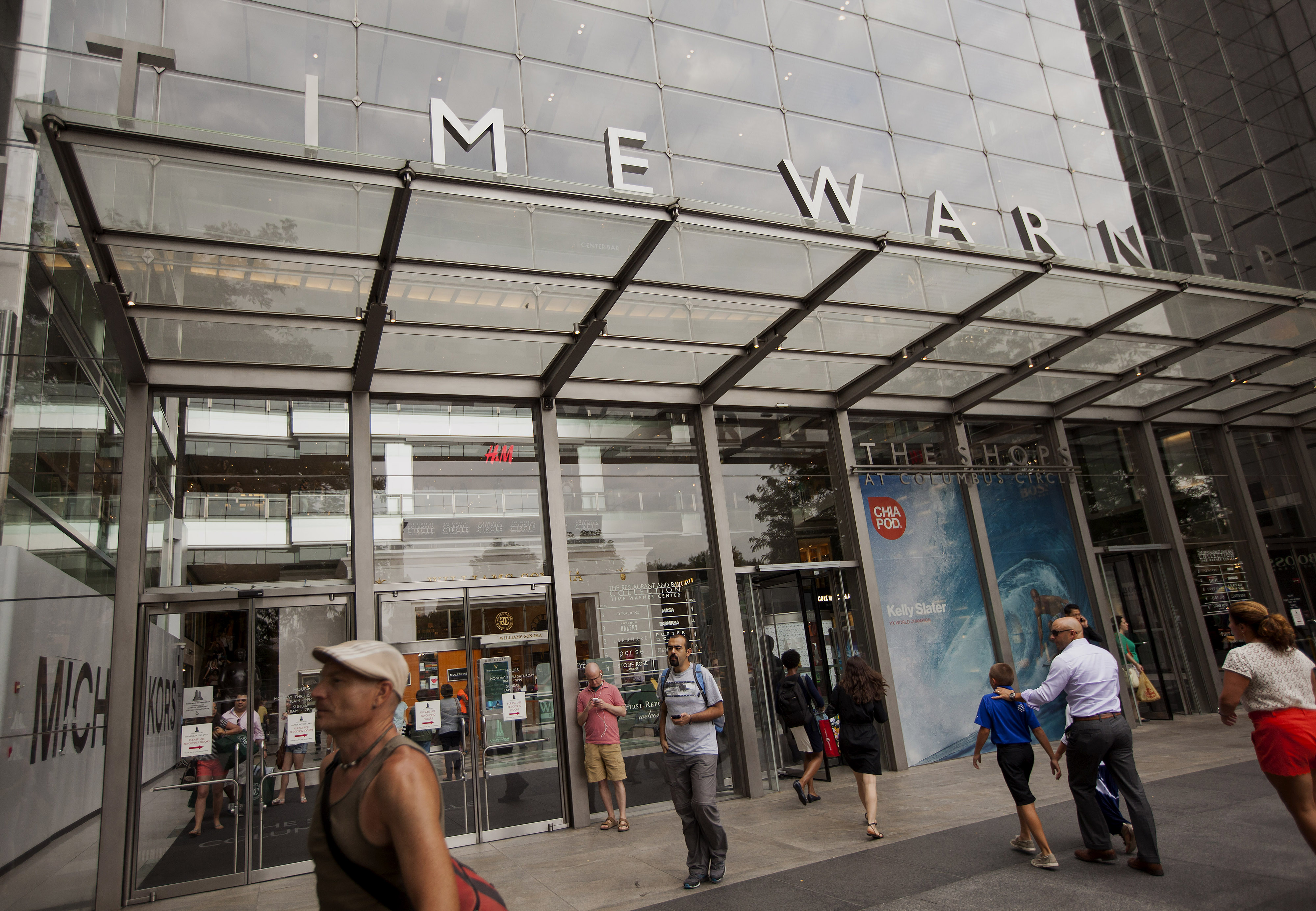 Pedestrians walk past the Time Warner Center in New York, U.S., on Monday, July 21, 2014.