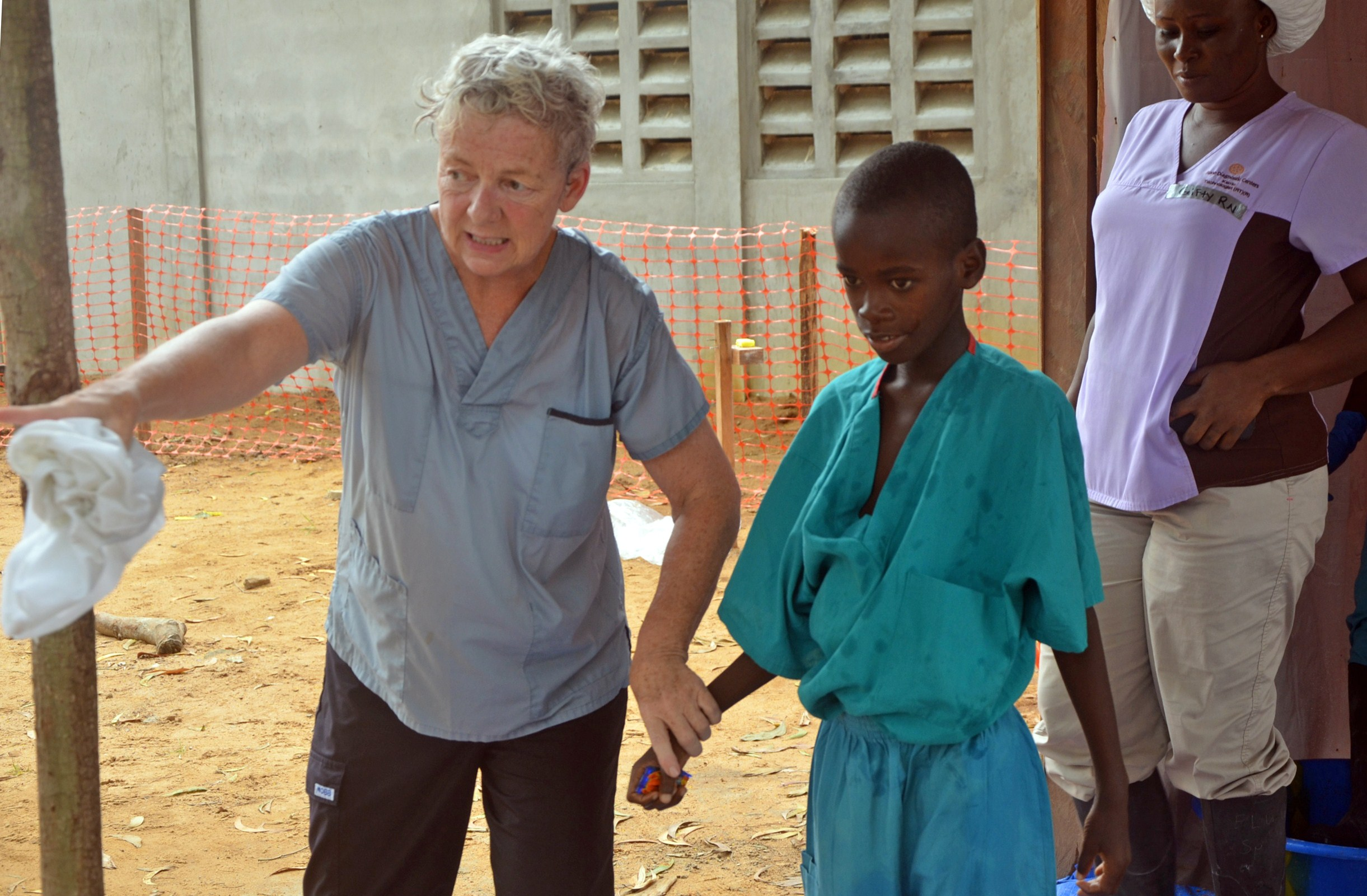 A 10-year-old boy walks with a doctor from Christian charity Samaritan's Purse after being taken out of quarantine and receiving treatment following his mother's death caused by the Ebola virus at the ELWA Hospital in the Liberian capital, Monrovia, on July 24, 2014