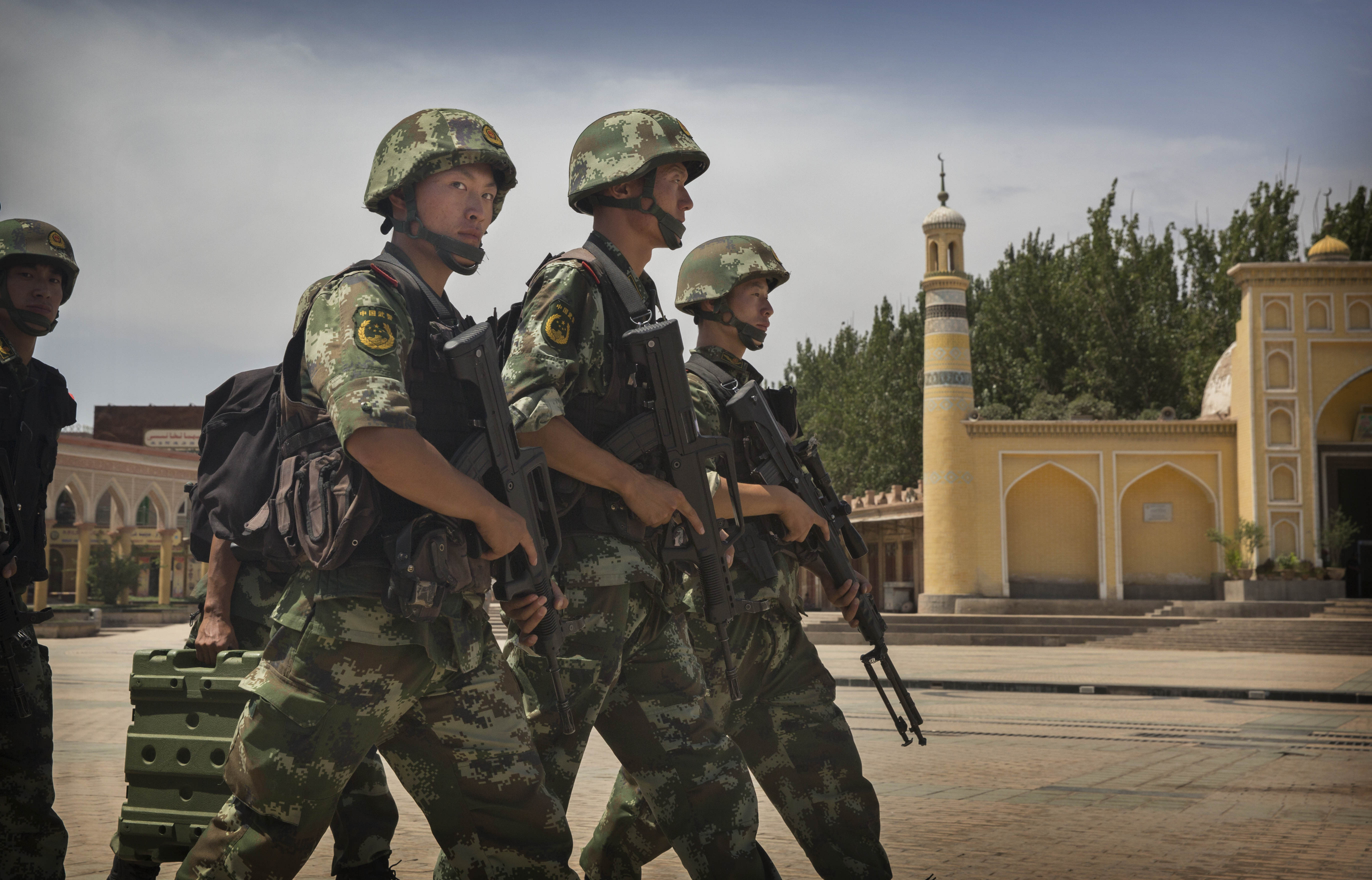 Chinese soldiers march in front of the Id Kah Mosque, China's largest, in Kashgar, on July 31, 2014. China has increased security in many parts of restive Xinjiang  following some of the worst violence in months