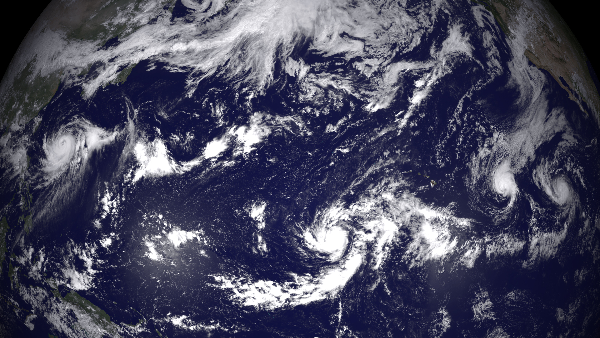 In this handout provided by the National Oceanic and Atmospheric Administration (NOAA) from the GOES-East satellite, four separate weather system  (L-R) Halong, Genevieve, Iselle, and Julio are tracked in the Pacific Ocean off the west coast of the United States
