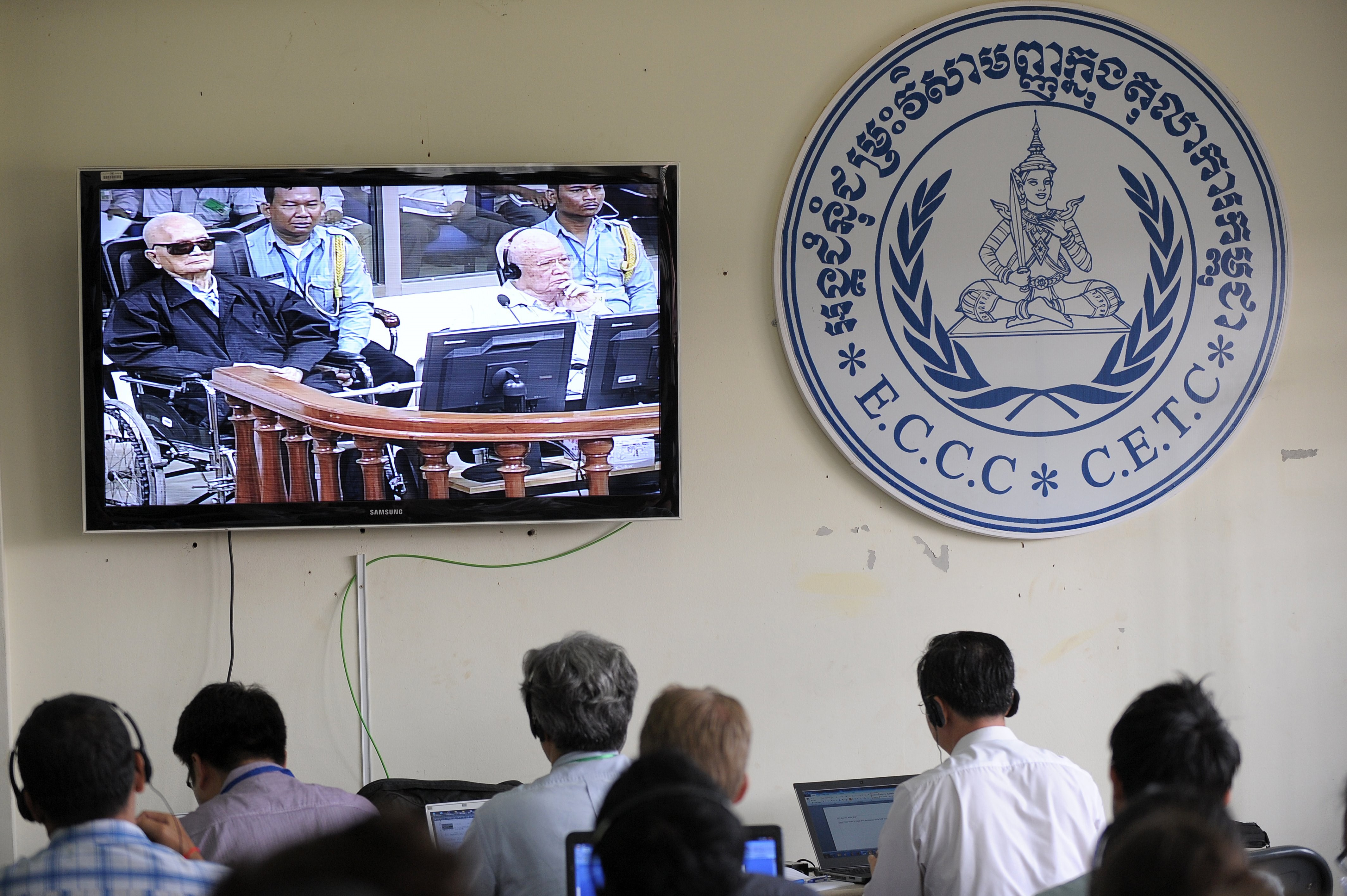 Cambodian and international journalists watch a live video feed showing former Khmer Rouge leader  Brother No. 2  Nuon Chea, left, and former Khmer Rouge head of state Khieu Samphan in the courtroom during their trial at the ECCC in Phnom Penh on Aug. 7, 2014.