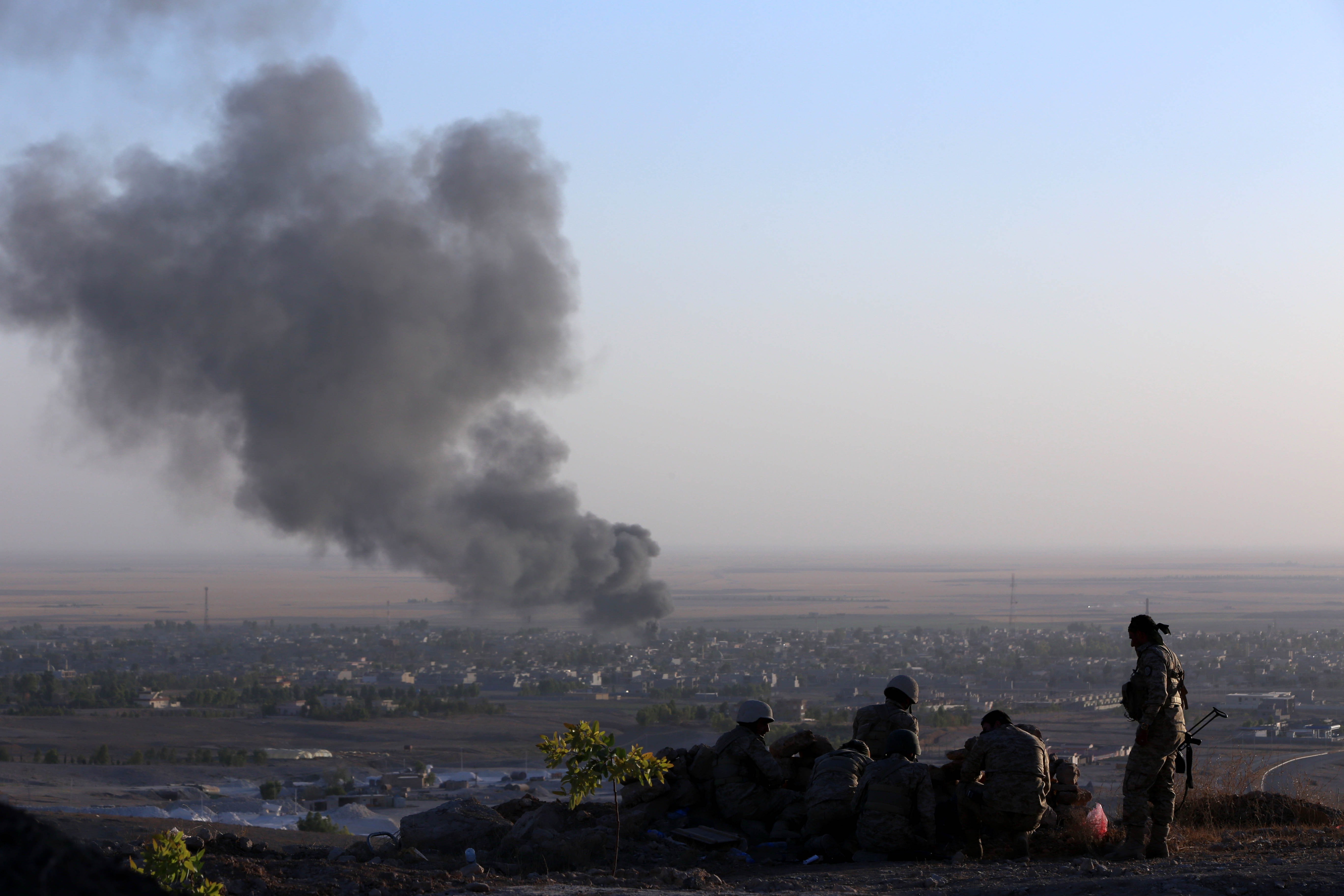 Iraqi Kurdish Peshmerga fighters look on as smoke billows from the town Makhmur, about 175 miles north of Baghdad, during clashes with ISIS militants on August 9, 2014
