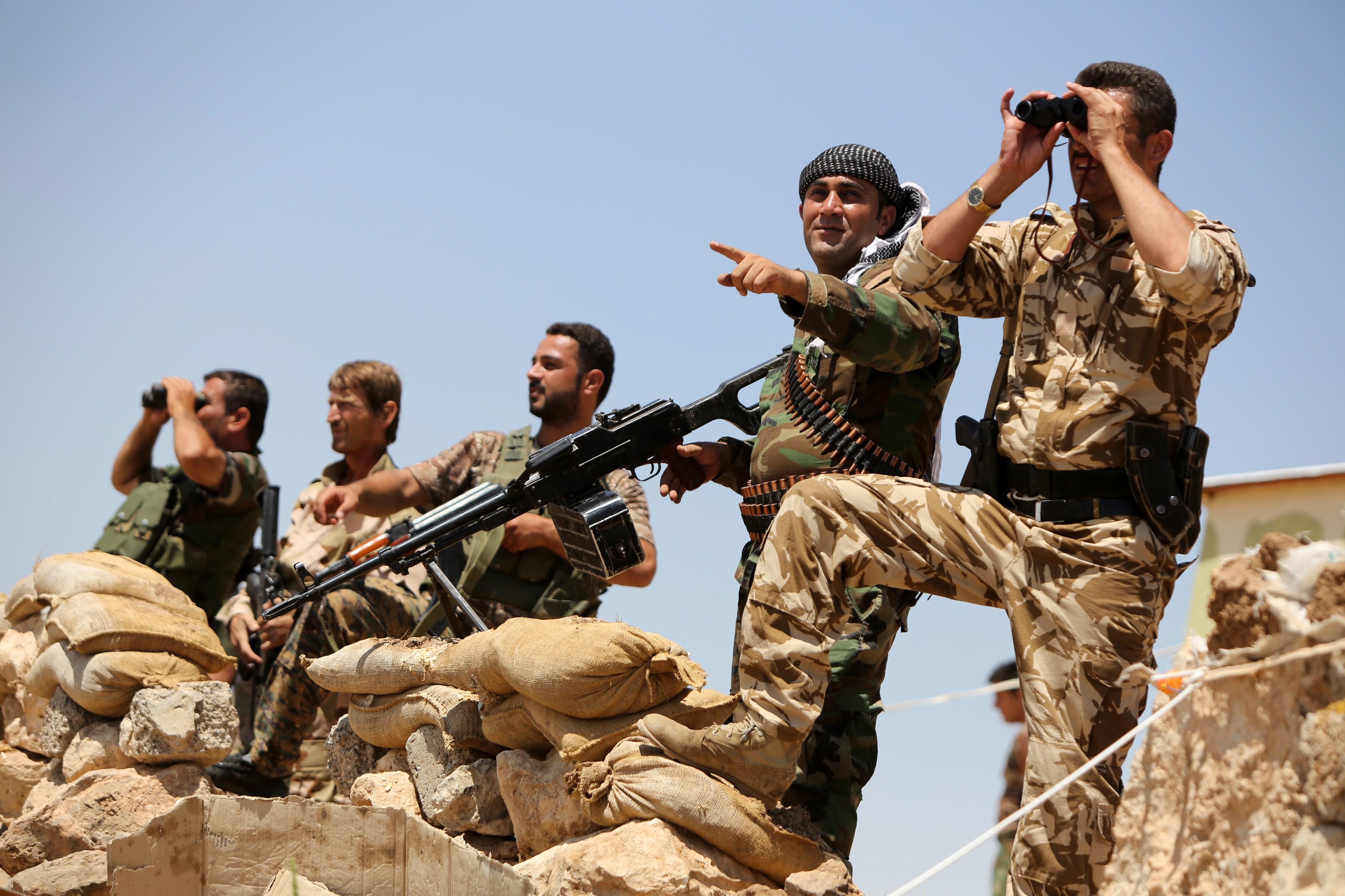 Iraqi Kurdish Peshmerga fighters take positions in northern Iraq on Tuesday.