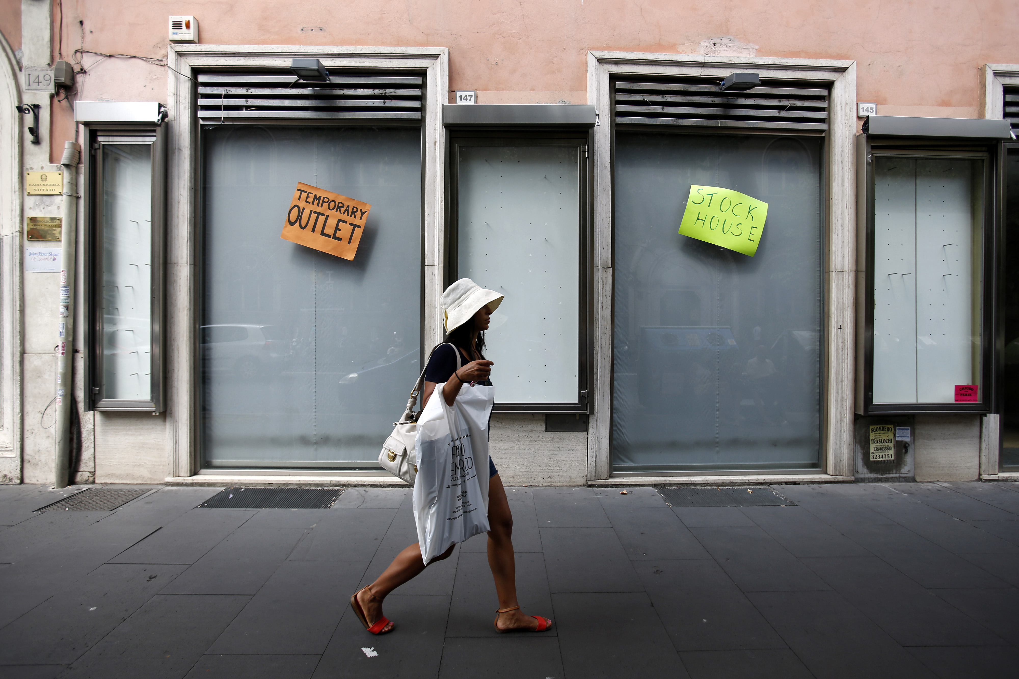 A pedestrian carries a plastic shopping bag as she passes a closed-down temporary outlet store in Rome, Italy, on Tuesday, Aug. 12, 2014. Italy's economy shrank 0.2 percent in the second quarter after contracting 0.1 percent in the previous three months.